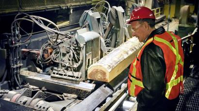 FILE PHOTO: Canadian Prime Minister Paul Martin watches logs being cut while visiting a sawmill in Richmond just south of Vancouver, British Columbia, Canada on December 14, 2005.