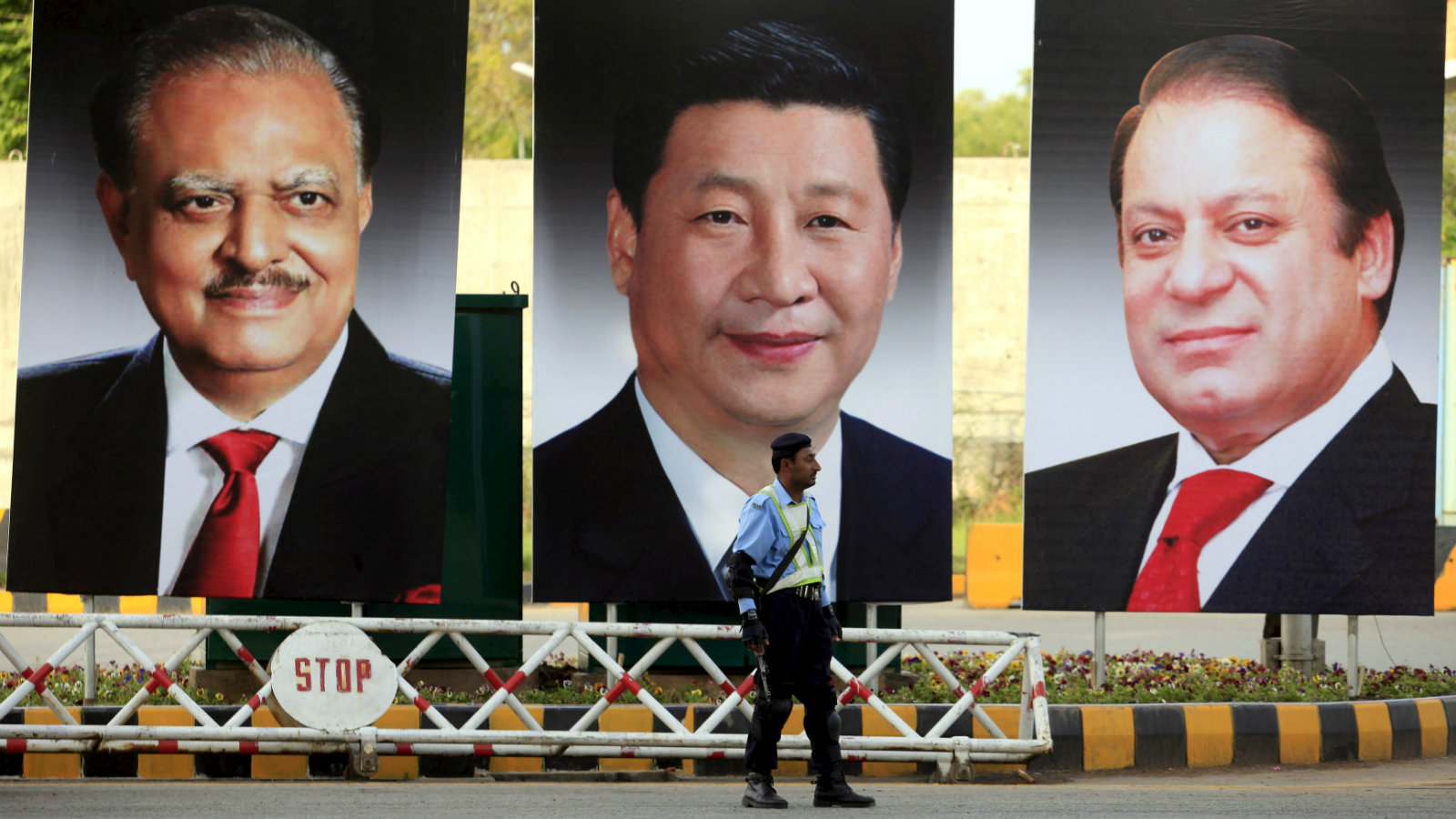 A policeman stands guard next to giant portraits of (L-R) Pakistan's President Mamnoon Hussain, China's President Xi Jinping, and Pakistan's Prime Minister Nawaz Sharif, displayed along a road ahead of Xi's visit to Islamabad April 19, 2015. Xi will visit Pakistan on April 20 on a two day official visit to meet Pakistani leadership.