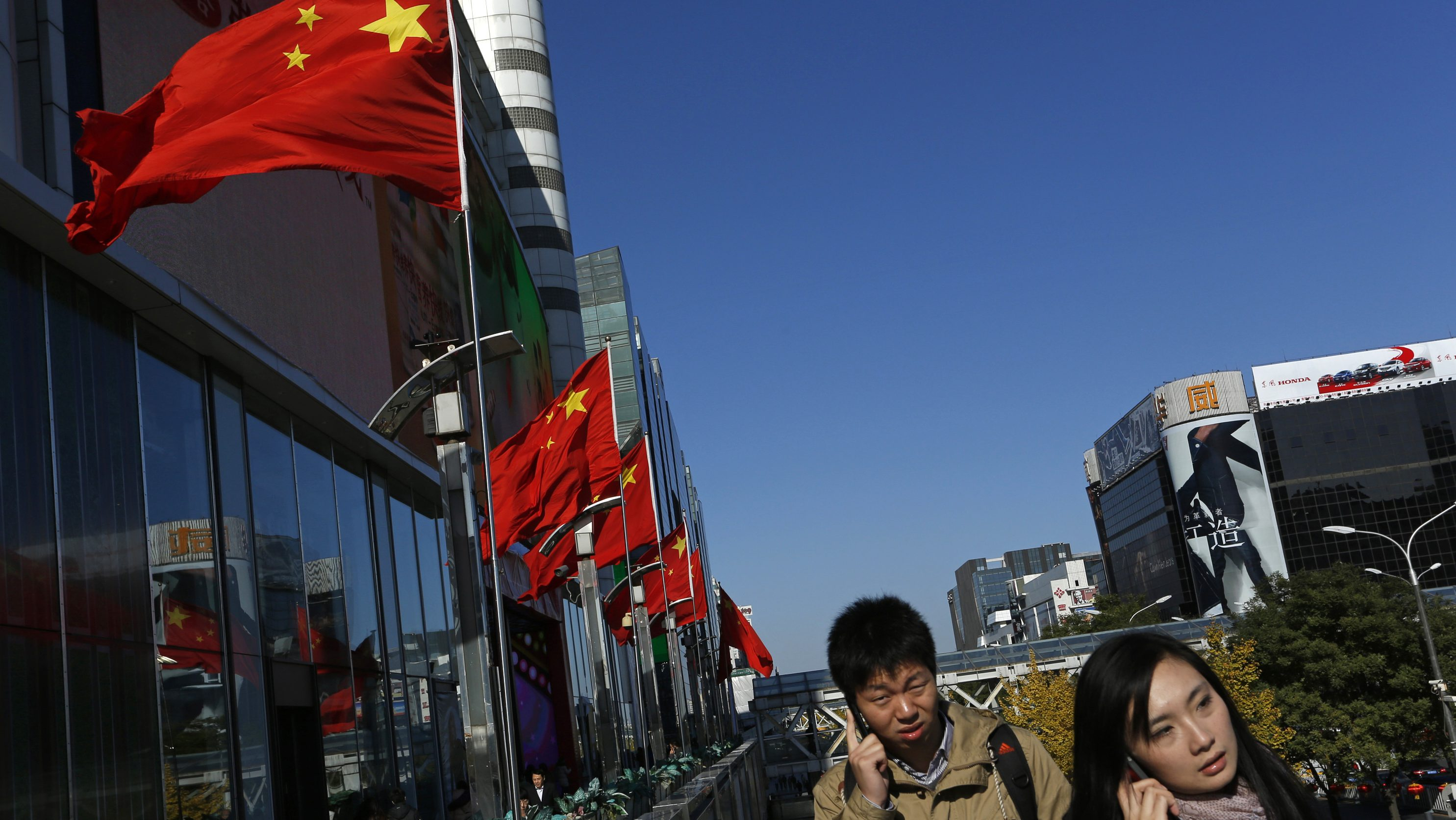 Chinese people talk on mobile phones outside a shopping mall in Beijing, China, Tuesday, Nov. 13, 2012. (AP Photo/Vincent Yu)
