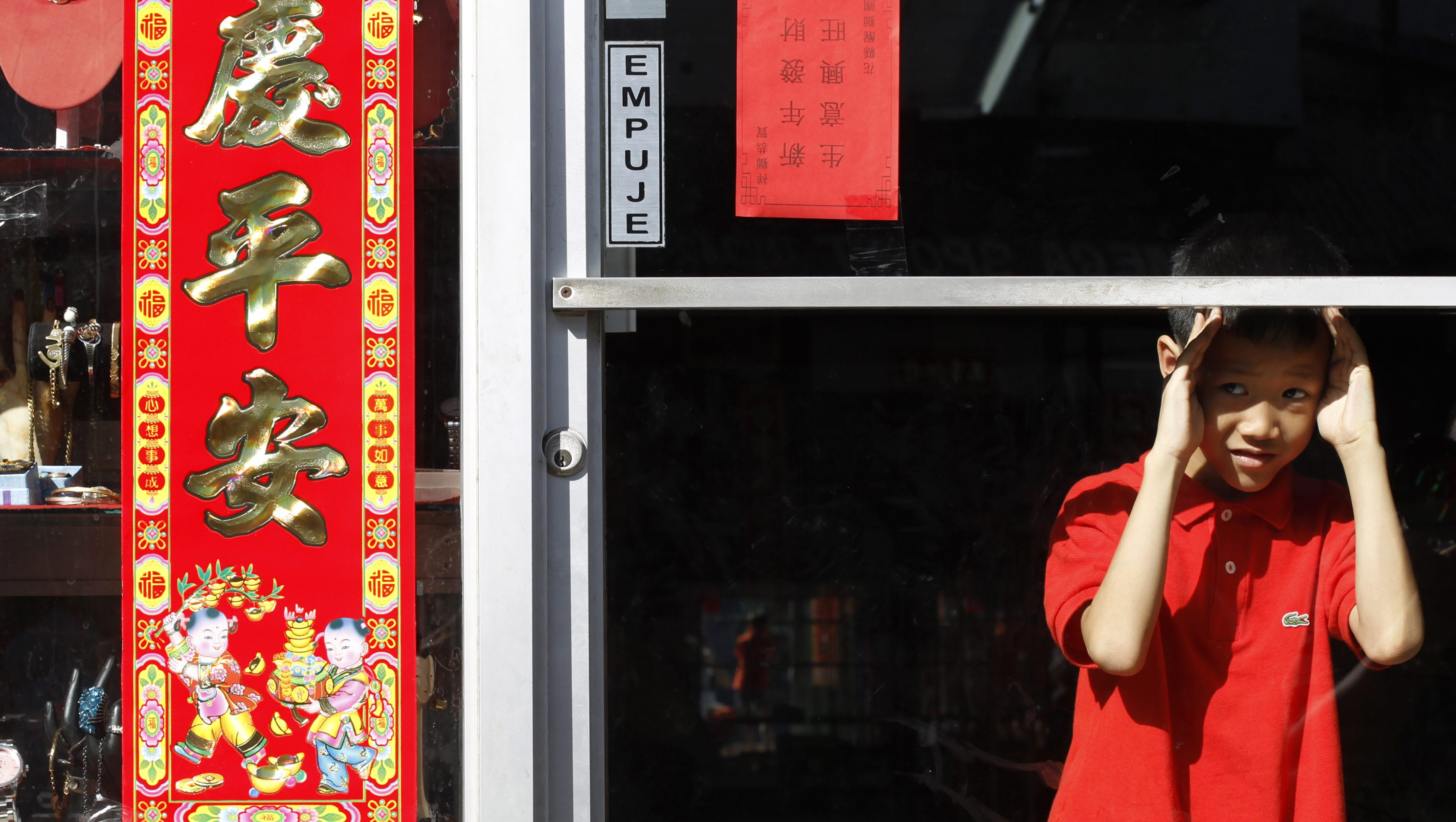 A boy looks through a shop glass door during the Chinese Lunar New Year celebrations at Chinatown in Panama City February 19, 2015. According to the lunar calendar, the Chinese New Year, which welcomes the year of the Sheep (also known as the Year of the Goat or Ram), falls on February 19 this year. REUTERS/Carlos Jasso (PANAMA - Tags: SOCIETY) - RTR4QB1T