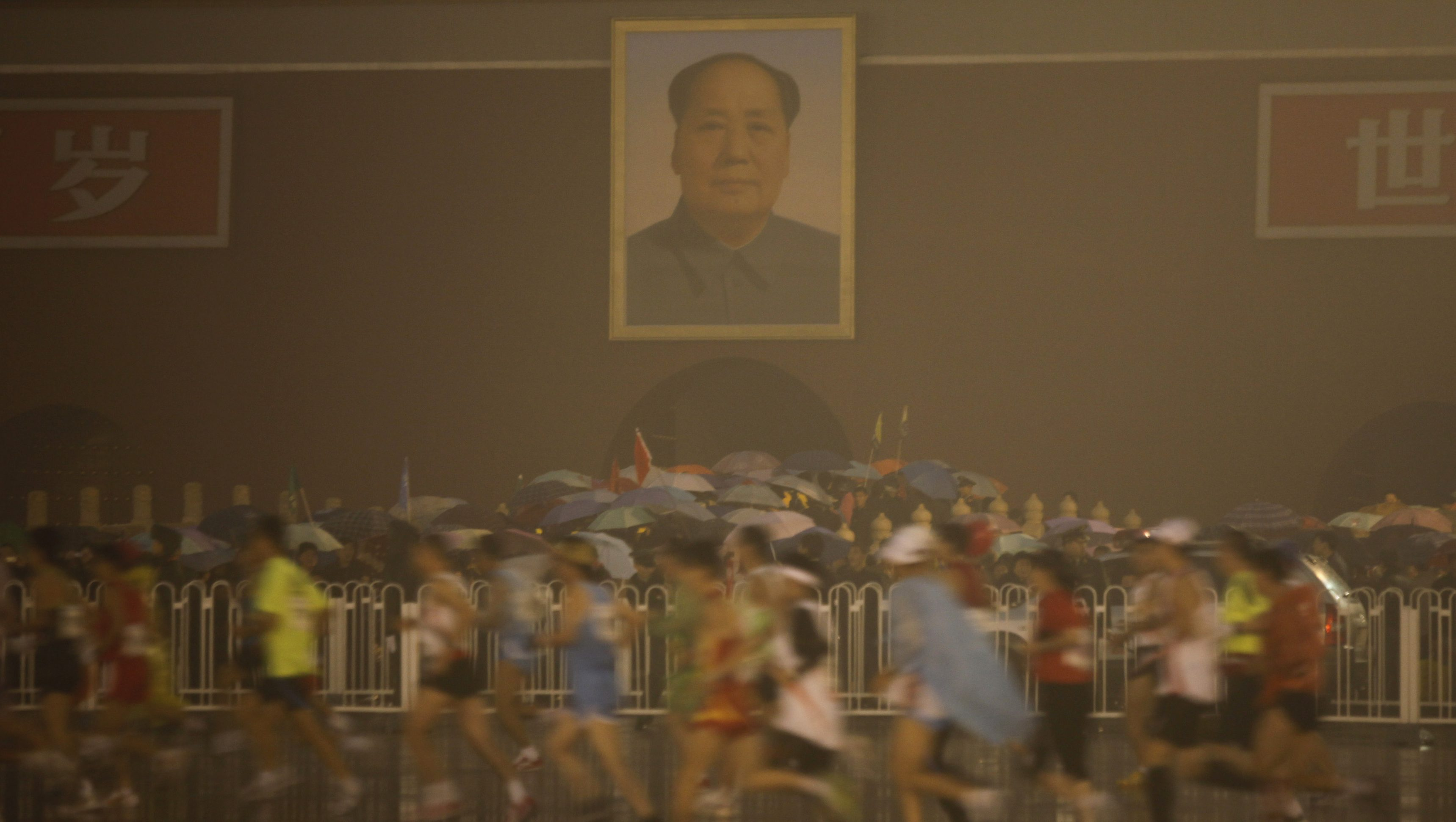 Participants run past the Tiananmen Gate in front of the portrait of late Chinese leader Mao Zedong during the 2010 Beijing Marathon on a rainy day in Beijing October 24, 2010. REUTERS/Grace Liang