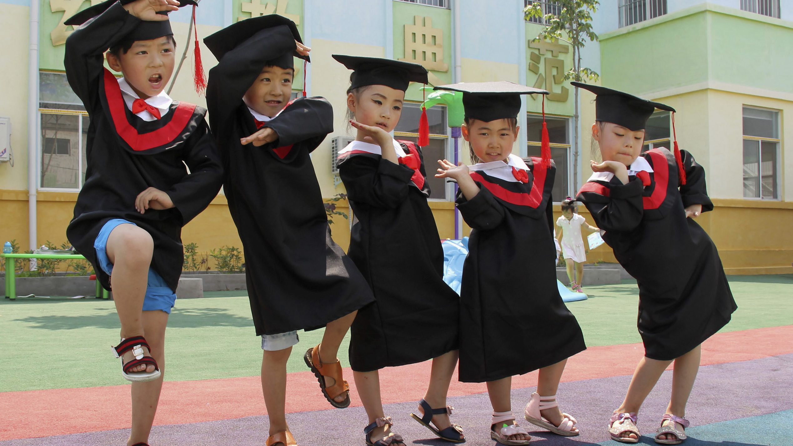 Children in gowns and mortarboards pose for pictures during their kindergarten graduation ceremony, in Wenxian county, Henan province July 2, 2014. Picture taken July 2, 2014. REUTERS/Stringer (CHINA - Tags: SOCIETY EDUCATION TPX IMAGES OF THE DAY) CHINA OUT. NO COMMERCIAL OR EDITORIAL SALES IN CHINA - RTR3WW0Z