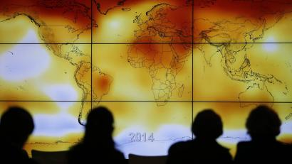 COP21 participants look at a screen showing a world map with climate anomalies during the World Climate Change Conference 2015 (COP21)