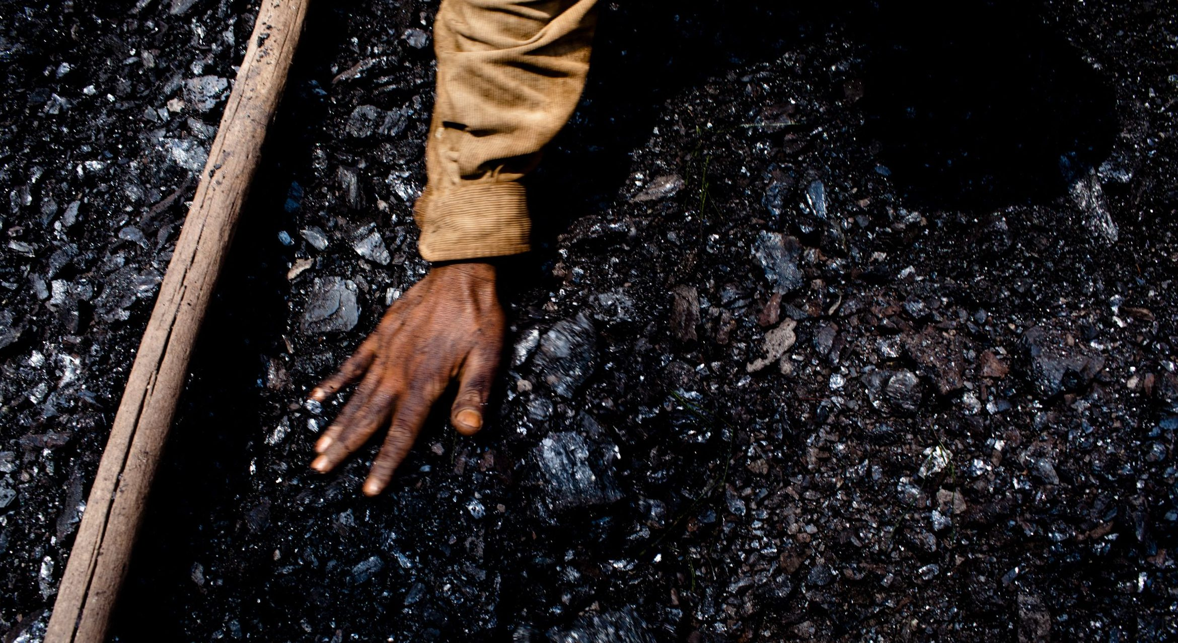 A hand touching a pile of coal