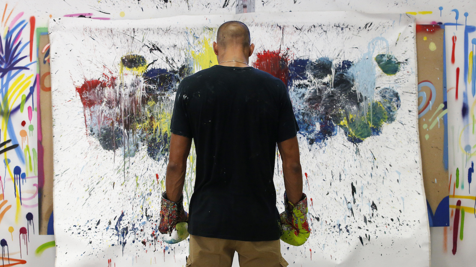 """In this photo taken on Tuesday, Sept. 6, 2016 Omar Hassan poses in front of his creation """"Breaking Through Milano"""" in his studio in Milan, Italy. When he creates art work, Omar Hassan doesn't get out paint brushes. He gets out his boxing gloves. Hassan, a 29-year-old artist and boxer, has combined his two passions, with the goal to bring the disciplines closer. Hassan, born in Milan to an Italian mother and Egyptian father, creates the works by dipping his glove in paint, and punching the canvas stretched over cardboard to keep it from breaking. He calls the series ''Breaking Through Milano'' His paintings sell from 8,000 to 40,000 euros, which he calls ''a great satisfaction, but not the goal.'' (AP Photo/Antonio Calanni)"""