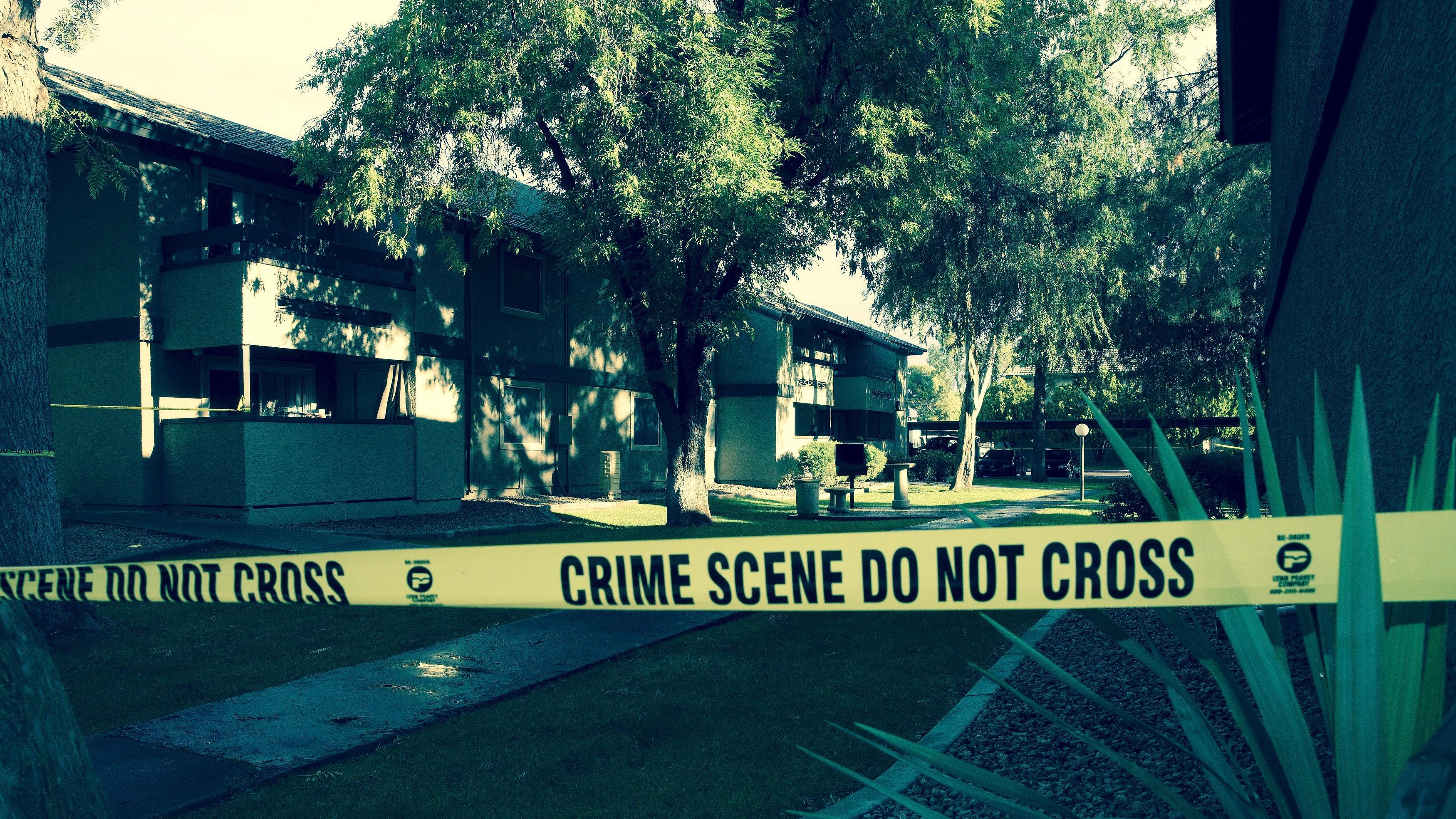 Crime scene tape surrounding house.