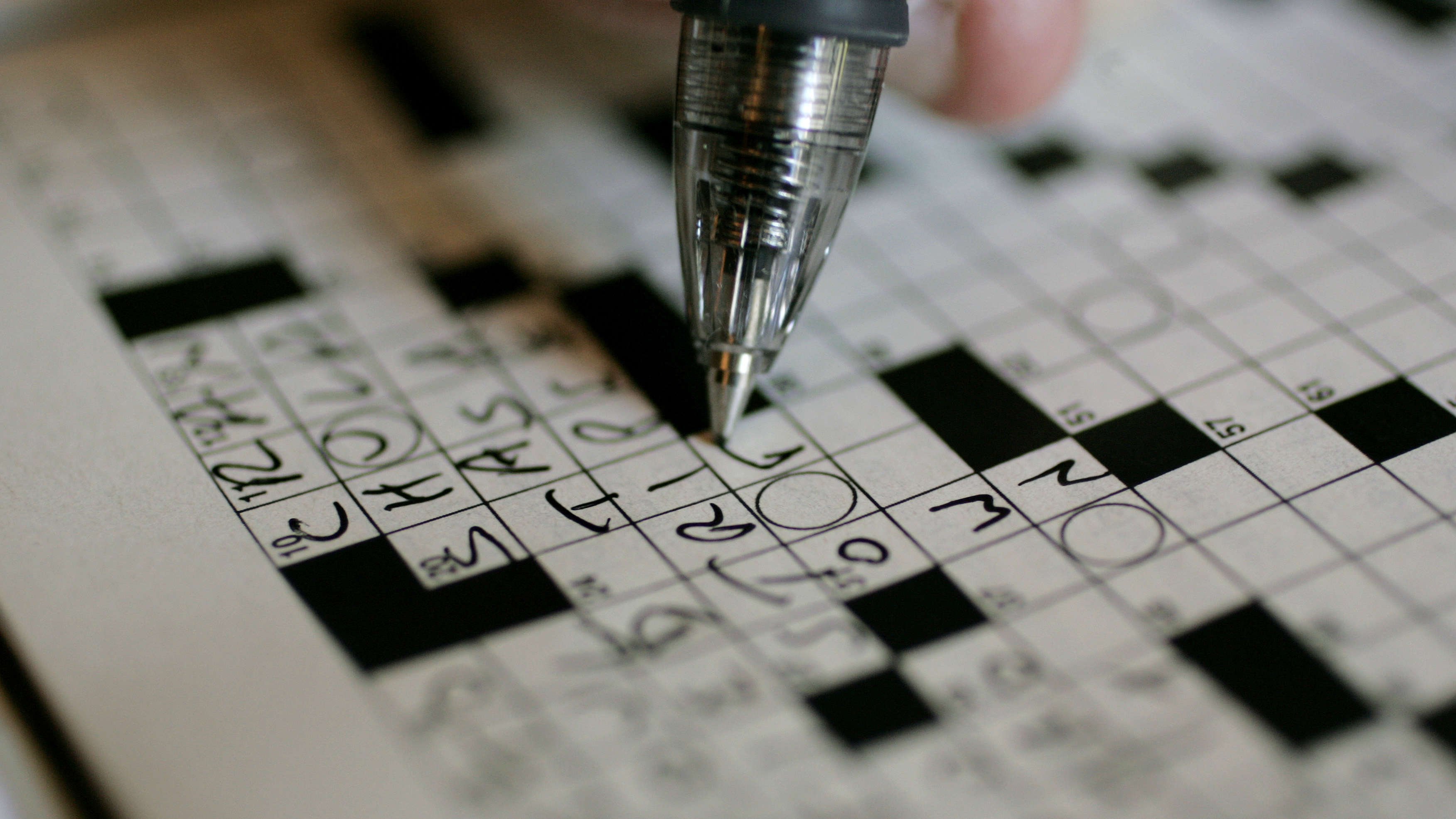 A pen touching a crossword puzzle