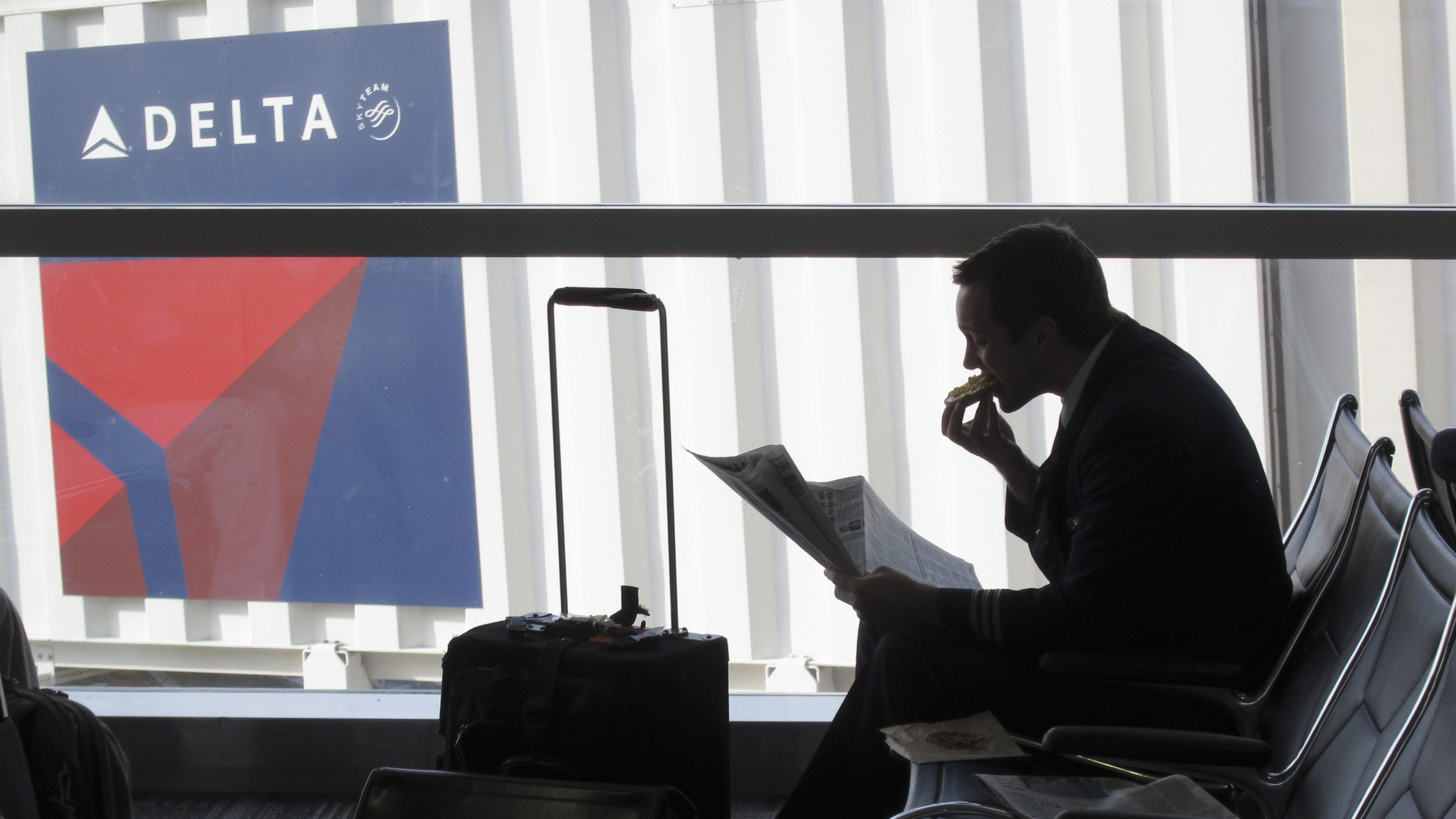 A passenger waits for his flight near a Delta Air Lines logo at Detriot Airport November 20, 2010.