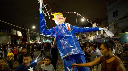"""People gather around as a woman prepares to light a figure of U.S. President Donald Trump rigged with fireworks, during a neighborhood celebration of """"the burning of Judas,"""" in central Mexico City, Saturday, April 15, 2017. The ancient Holy Week tradition, in which the sins and evils of the previous year are ritually cleansed, features figures of devils, politicians, and cartoon characters. This year Trump was a repeated motif, in one representation with a brick wall for a head, in another as a jack-in-the-box, and in a third as a severed head held aloft by a devil"""