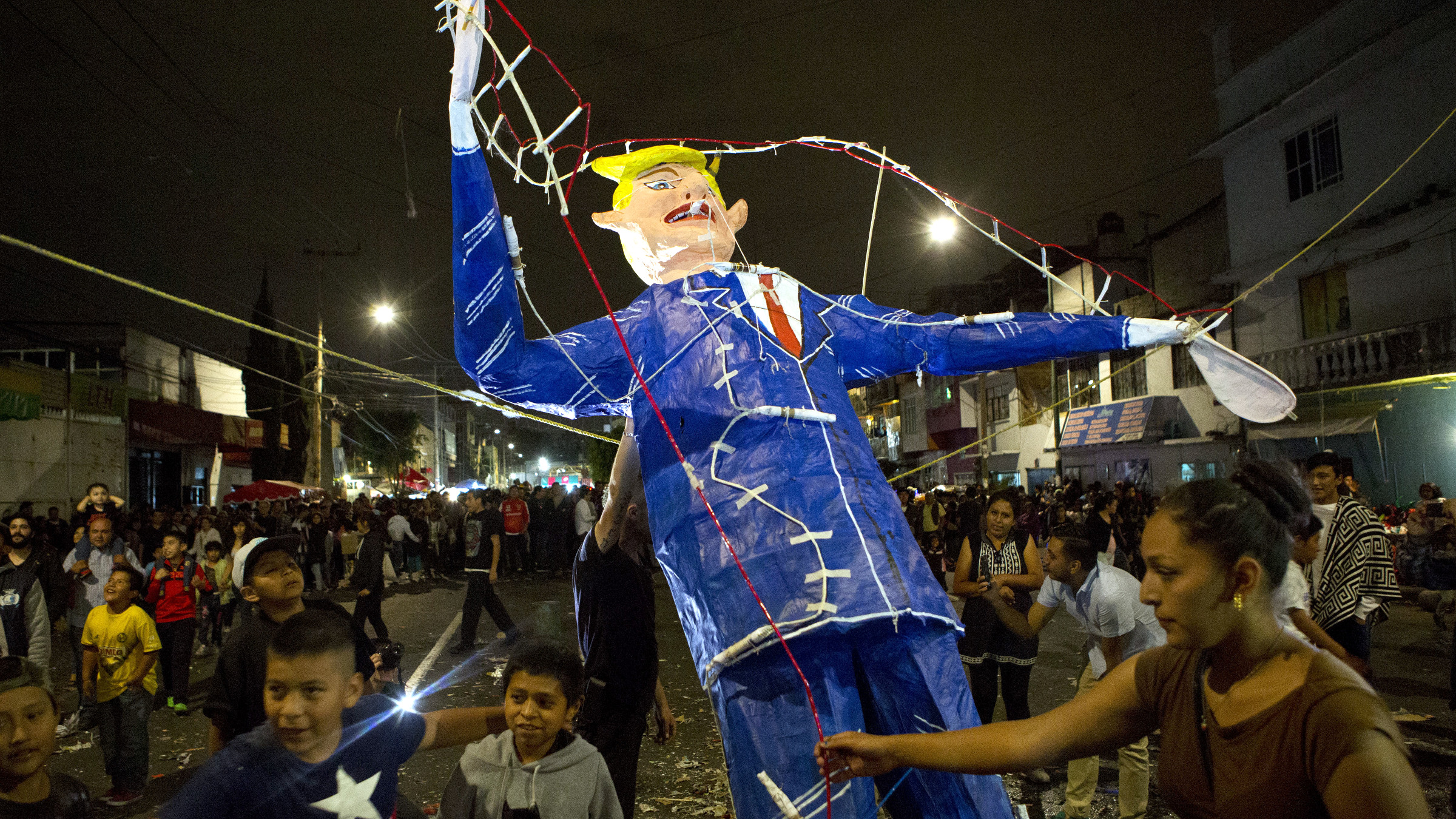 "People gather around as a woman prepares to light a figure of U.S. President Donald Trump rigged with fireworks, during a neighborhood celebration of ""the burning of Judas,"" in central Mexico City, Saturday, April 15, 2017. The ancient Holy Week tradition, in which the sins and evils of the previous year are ritually cleansed, features figures of devils, politicians, and cartoon characters. This year Trump was a repeated motif, in one representation with a brick wall for a head, in another as a jack-in-the-box, and in a third as a severed head held aloft by a devil"
