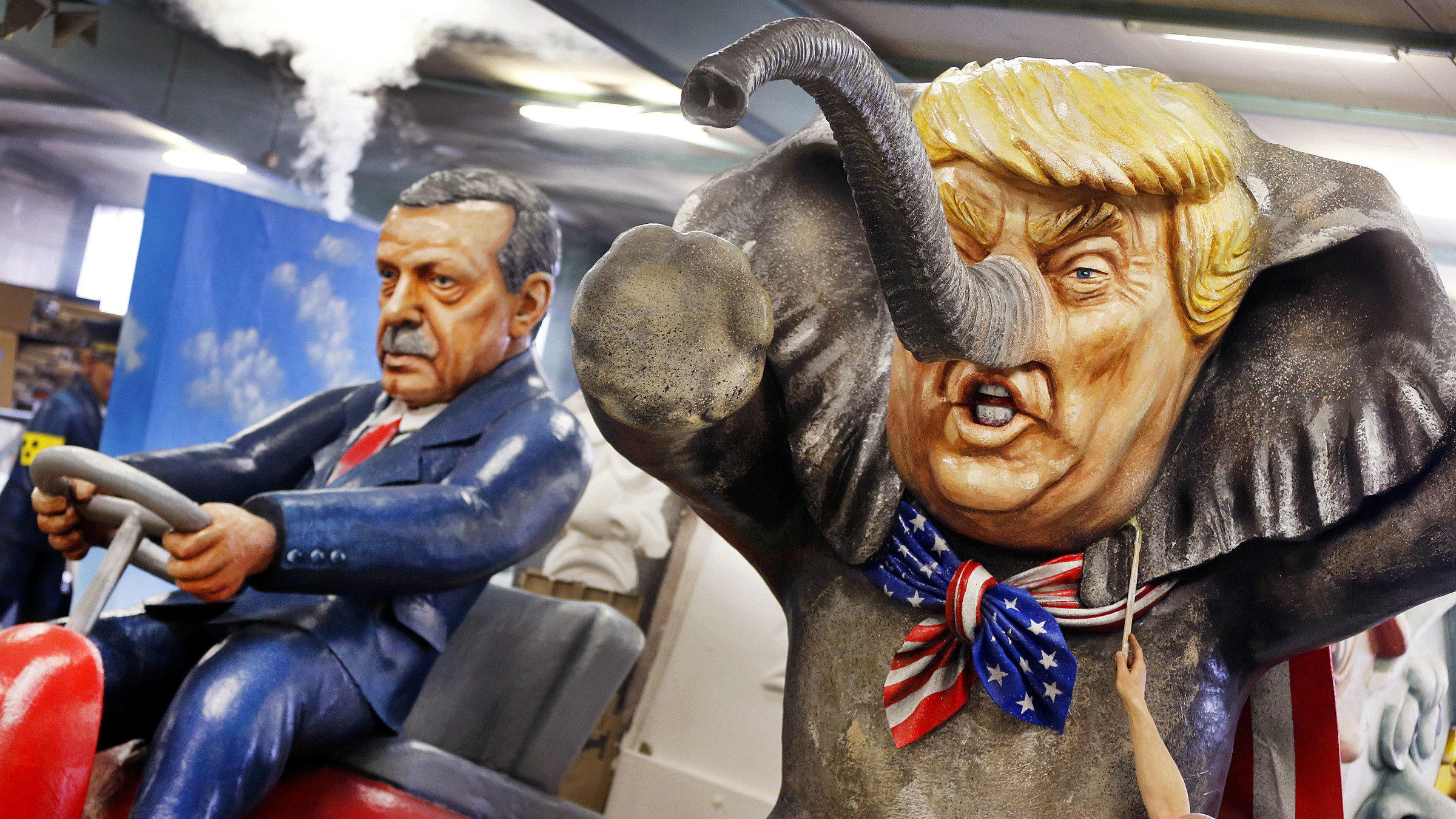 A worker poses with a brush in front of a figure depicting US President Donald Trump as an elephant and Turkish President Erdogan sitting on a bobby car during a press preview in a hall of the Main carnival club in Mainz, Germany, Tuesday, Feb. 21, 2017. The figure is part of various carnival floats of the Rose Monday procession in Mainz.