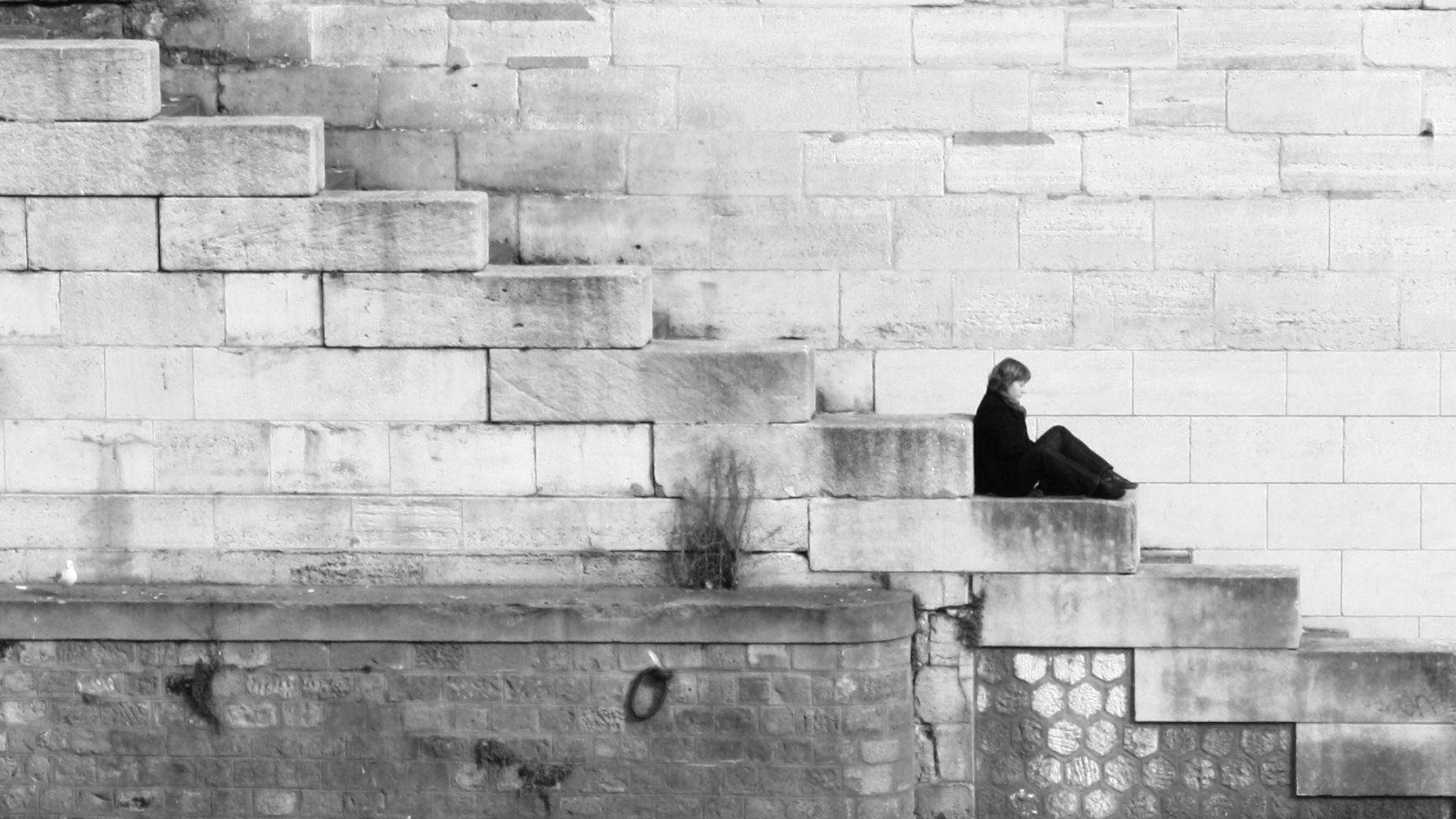 A woman sits on stairs by a river