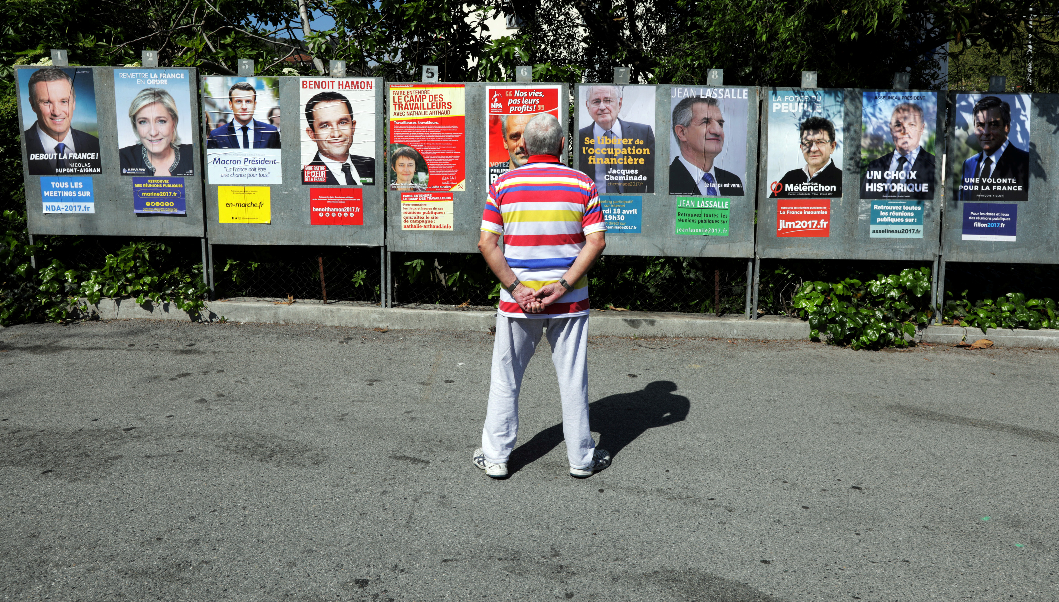 A man looks at campaign posters of the 11th candidates who are running in the 2017 French presidential election, in Saint Andre de La Roche