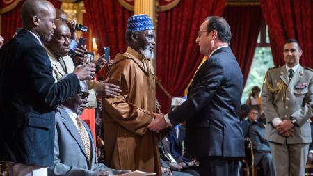 French President Francois Hollande (C-R)shakes hands with veterans during a ceremony to award French citizenship to former Senegalese riflemen veterans at the Elysee Palace in Paris, France, 15 April 2017.