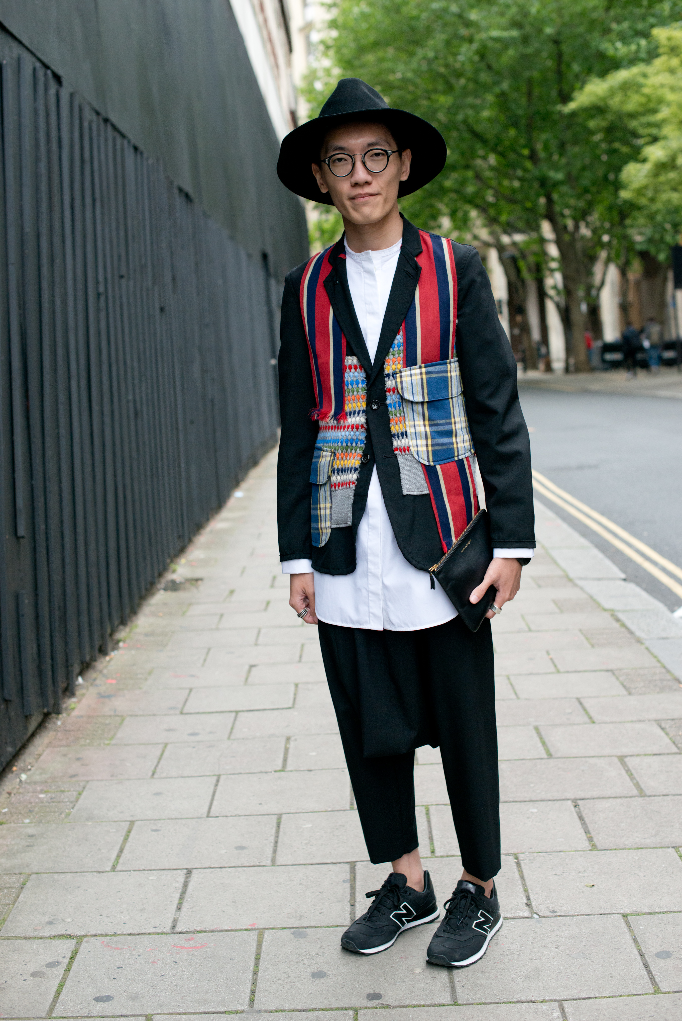 LONDON, ENGLAND - JUNE 16: Student Yongyang Hoon wears Comme Des Garcon trousers, coat and bag, New Balance trainers, Celine shirt and Reinhard Plank hat on day 2 of London Collections: Men on June 16, 2014 in London, England. (Photo by Kirstin Sinclair/Getty Images)