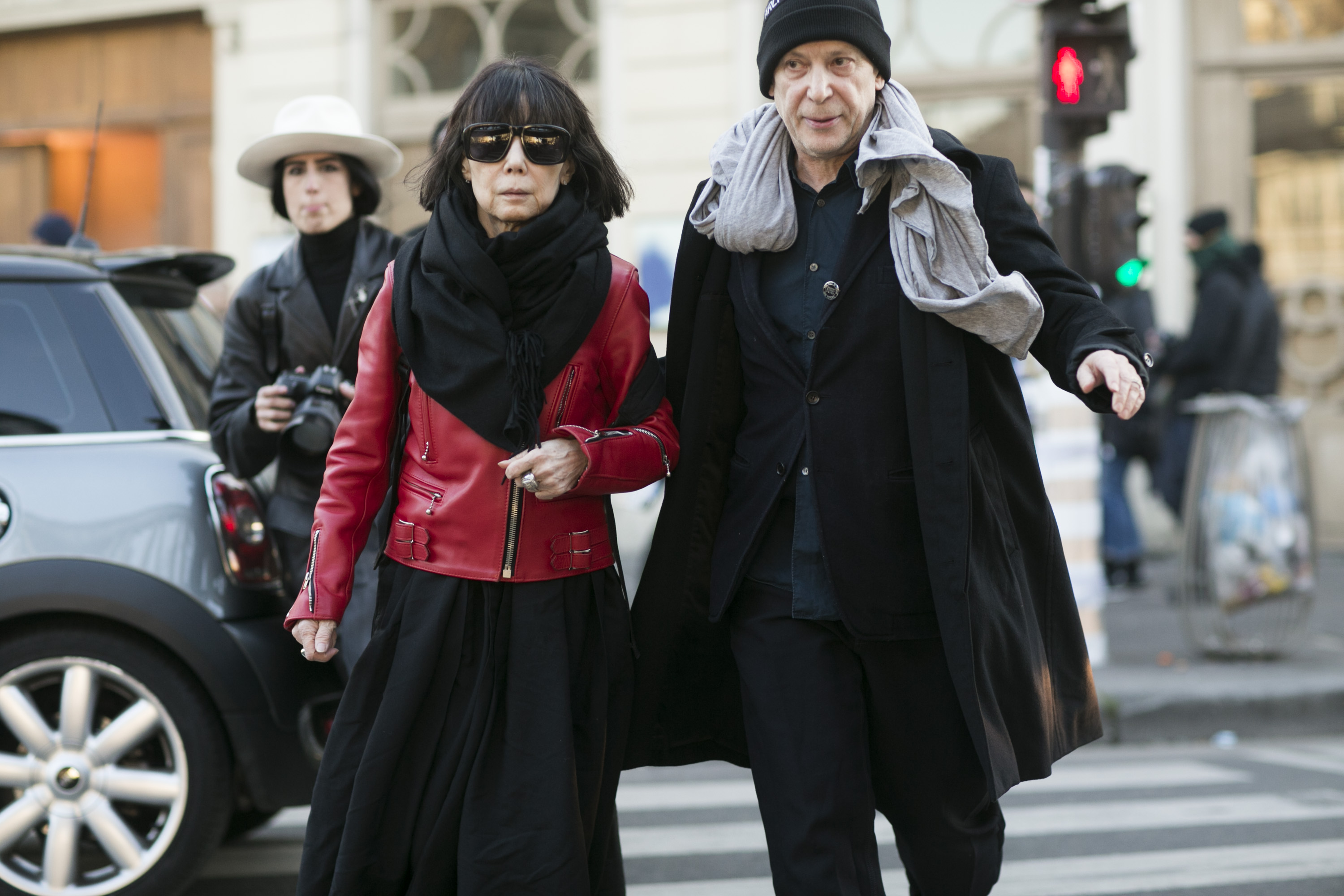 PARIS, FRANCE - JANUARY 21: Rei Kawakubo, Comme des Garcons creative director, and Adrian Joffe, Dover Street Market and Comme des Garcons president, exit the Gosha Rubchinskiy show on January 21, 2016 in Paris, France. Rei wears a red Comme des Garcons leather jacket, black sunglasses, a black scard, and black dress. (Photo by Melodie Jeng/Getty Images)