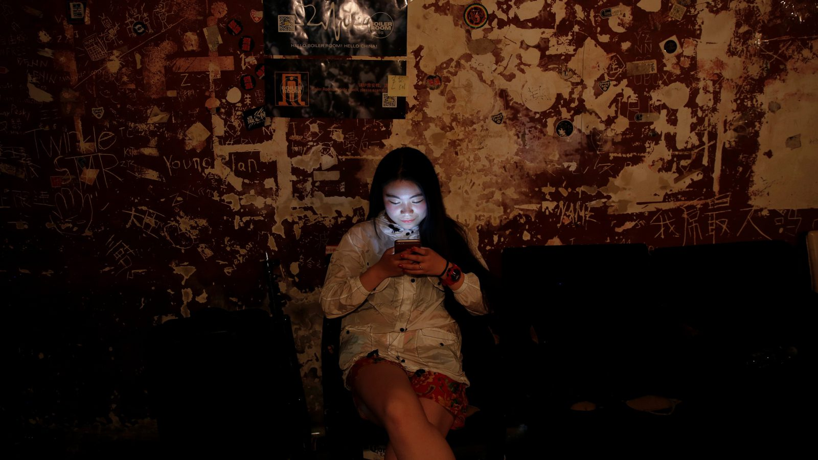 """A girl uses her phone at Mao Live House during its last public concert night in central Beijing, China April 24, 2016. Mao Live House, a prominent live rock music venue in Beijing, shut its doors on the weekend, the latest closure to hit China's rock music scene. Owner Li Chi said the club, popular among fans of punk, metal and alternative rock since it opened nine years ago, was forced to close due to tighter rules on live performances. REUTERS/Damir Sagolj      SEARCH """"MAO LIVE"""" FOR THIS STORY. SEARCH """"THE WIDER IMAGE"""" FOR ALL STORIES  - RTX2CLFE"""
