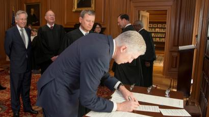 Neil Gorsuch signing a document at a table.
