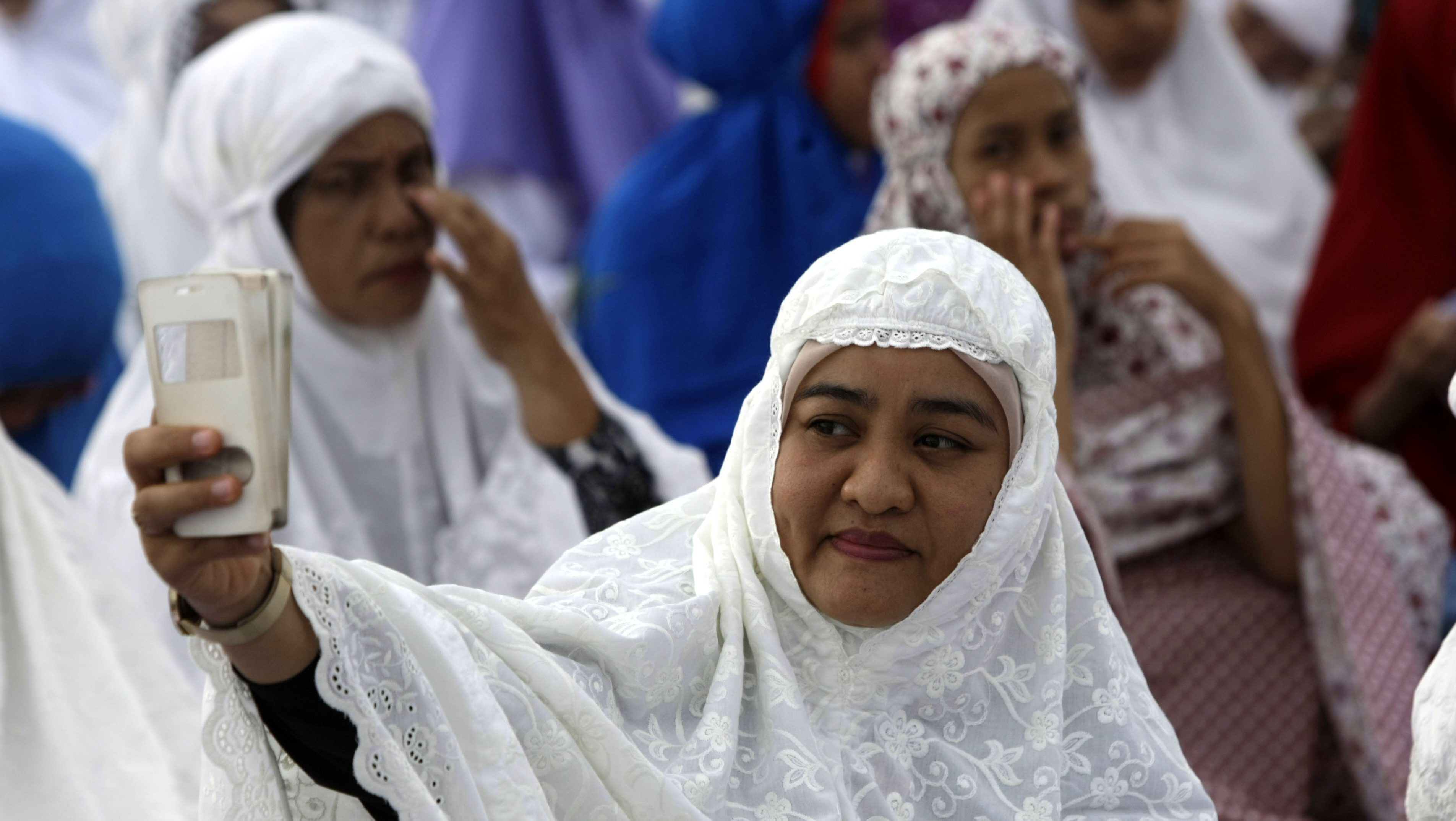A picture made available 26 September 2016 shows a Muslim woman taking a selfie during a mass prayer session, in Banda Aceh, Indonesia, 12 September 2016. South-east Asian nations are cashing in on increasing earnings in the tourism sector from Islamic travelers, and 'Halal Tourism' is reported to be among the fastest growing travel groups. Among other things on offer to Muslim travelers is halal food permitted by Islam, available in specially dedicated restaurants and shops, with no alcohol, and accommodation enabling suitable places for prayer, male and female segregation such as women-only swimming pools and private beaches, conservative uniforms for hotel serving staff, and copies of the Koran in rooms. United Nations World Tourism Day celebrations will be observed on 27 September 2016.