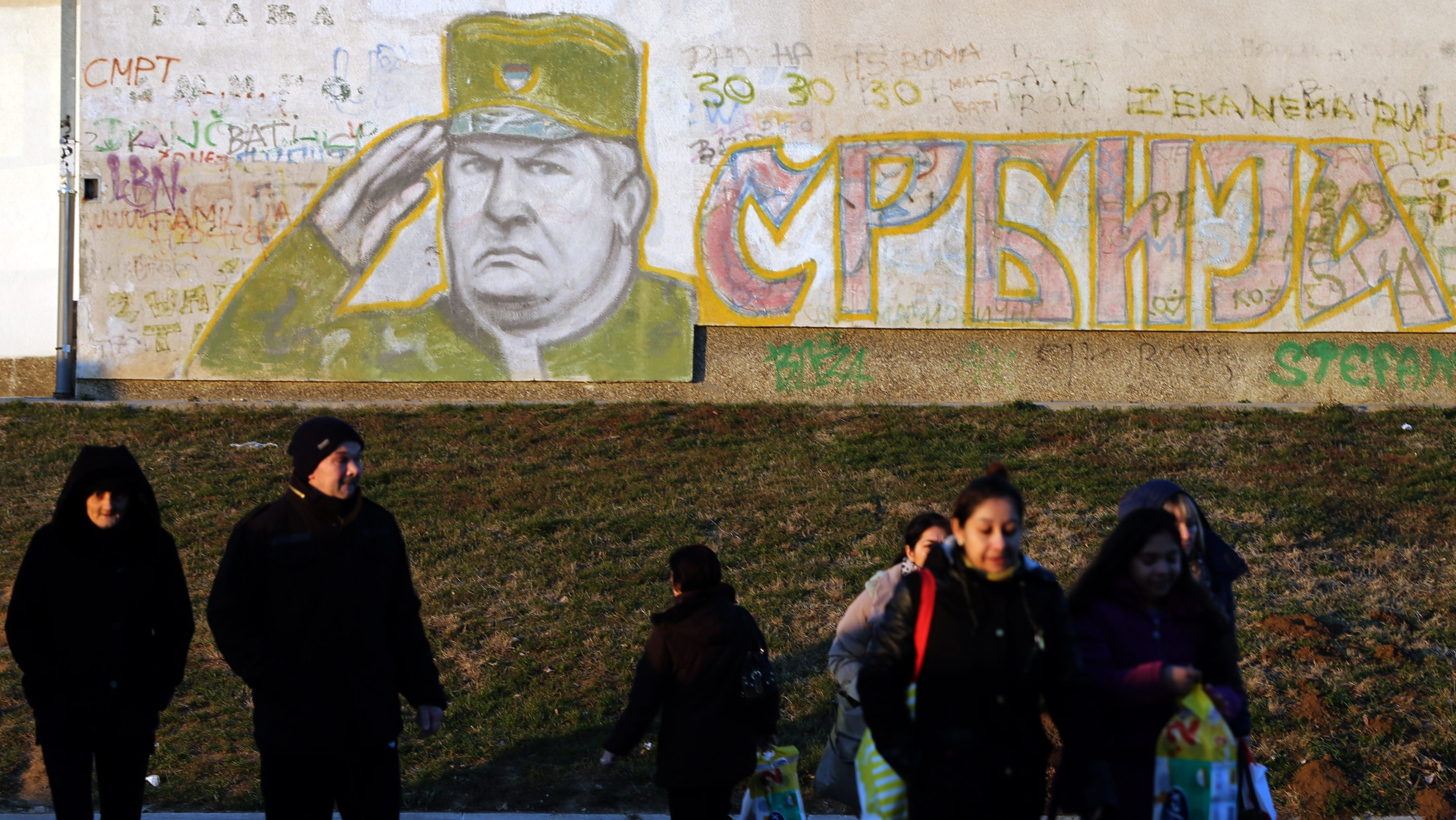 epa05667661 People walk in front of a mural depicting Serbian General Ratko Mladic, a war-time Bosnian Serb military commander, in a suburb of Belgrade, Serbia, 12 December 2016. Mladic, who is tried for warcrimes committed in Bosnia and Hercegovina between 1992-1995, is to start his defense plea in the trial at the International Criminal Tribunal for the former Yugoslavia (ICTY) in The Hague, The Netherlands. According to media reports the chief prosecutor in the trial on 07 December had called for a lifetime imprisonment for Mladic for his involvement in the Srebrenica masacre.  EPA/KOCA SULEJMANOVIC