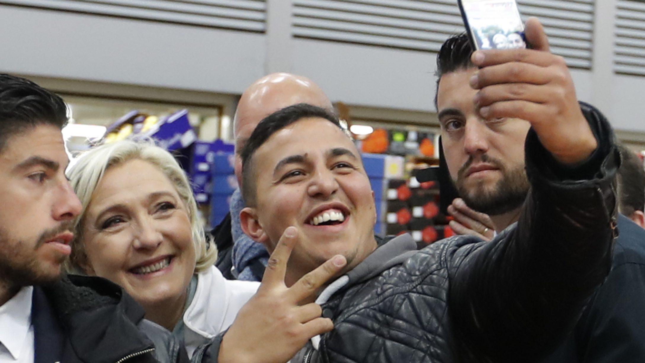 epa05926483 Marine Le Pen (2-L), French National Front (FN) political party candidate for French 2017 presidential election, poses for a selfie with an employee as she visits the Rungis international food market, near Paris, during her campaign, France, April 25, 2017.  EPA/CHARLES PLATIAU / POOL MAXPPP OUT