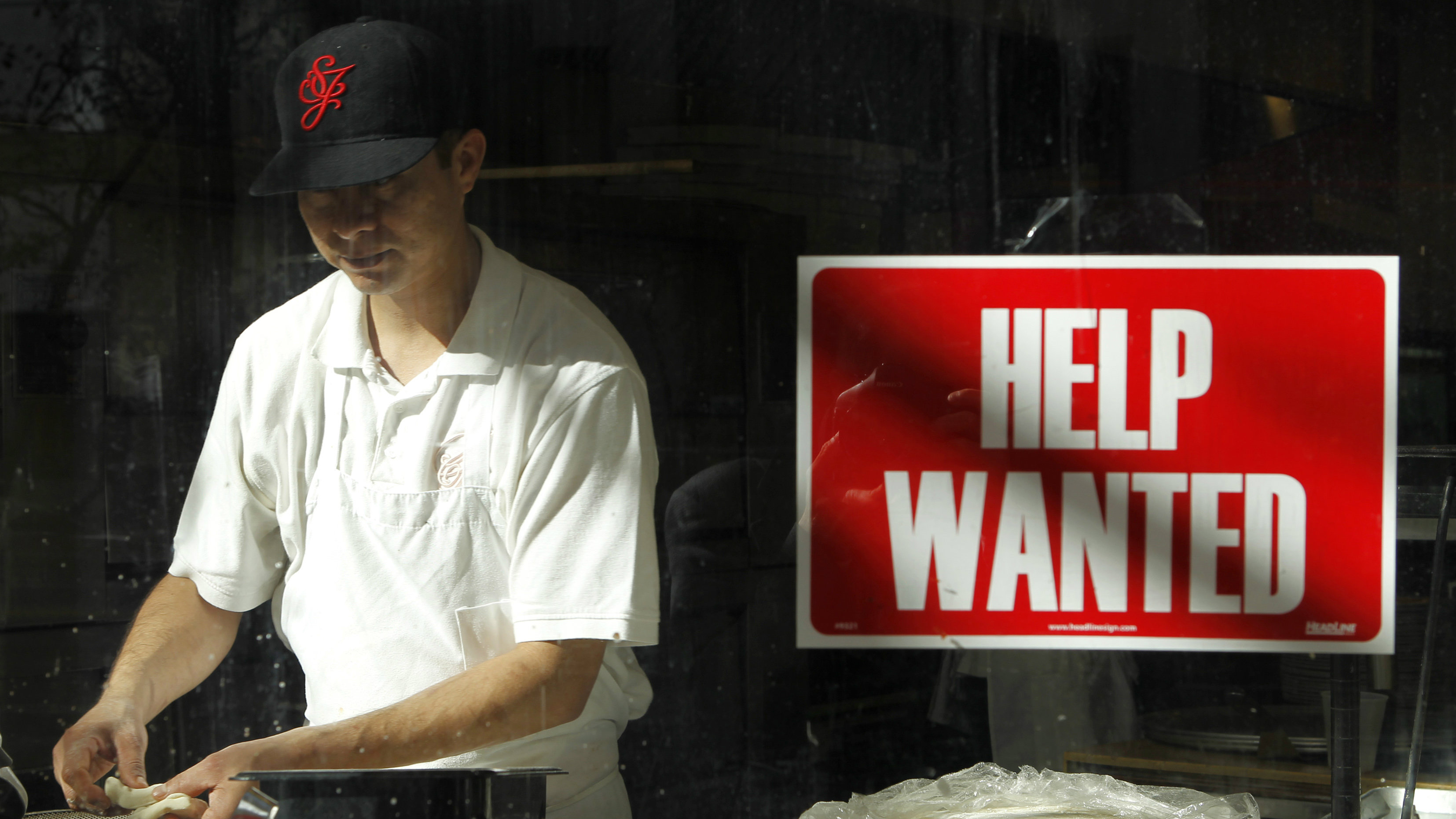 A man prepares a meal near a help wanted sign hanging in a restaurant window in San Francisco,
