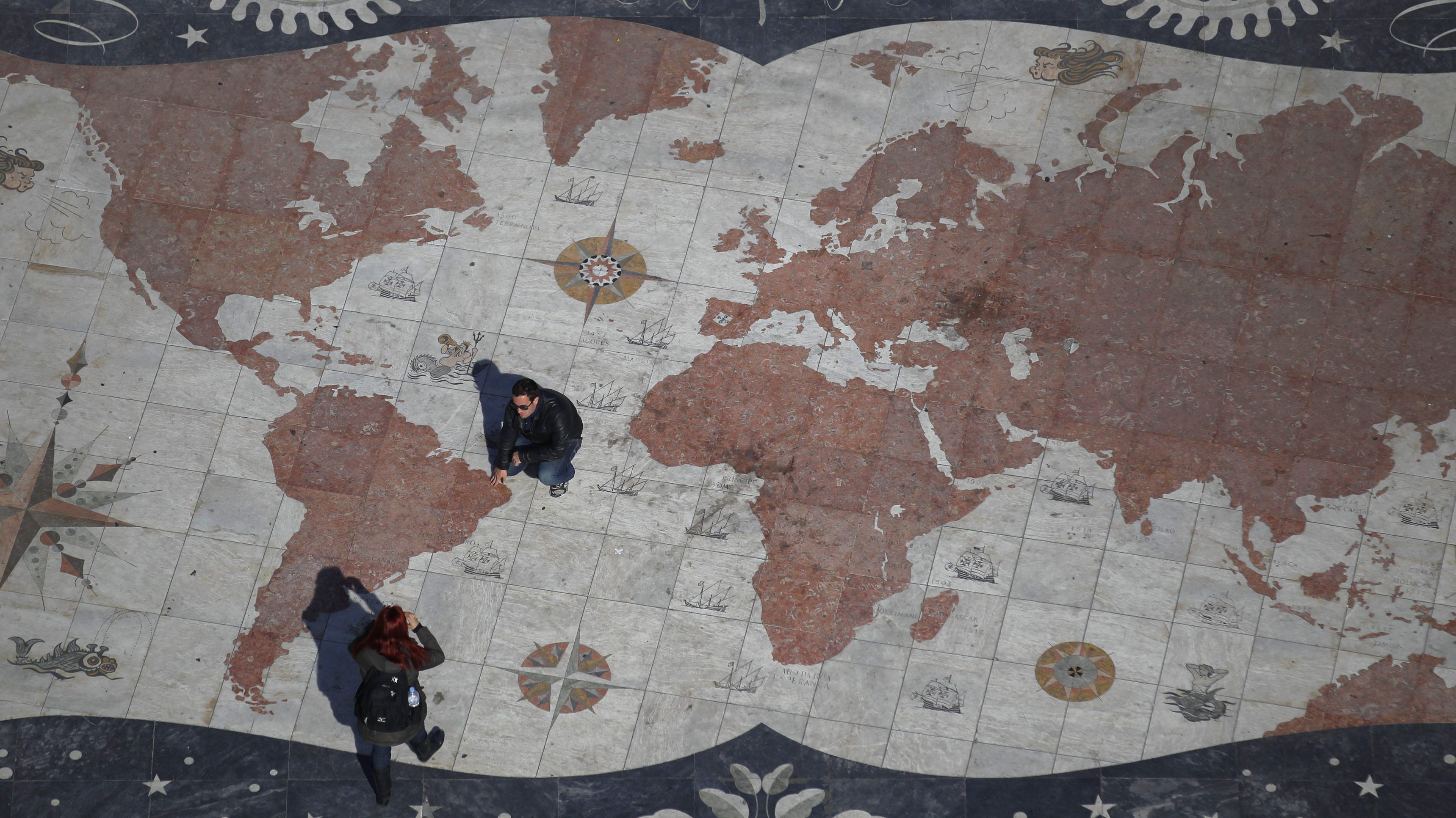 A man is photographed on a square decorated with a giant world map, with marks showing former Portuguese colonies, in Lisbon March 6, 2012. Portugal flourished as a global power with explorers like Vasco da Gama and Pedro Alvares Cabral building an empire which lasted for 600 years. Now a new wave of adventurers is once again seeking work, and hopefully fortune, elsewhere. Emigrating is fast becoming a preferred option for many seeking a decent living as their bailed-out economy suffers under debt, low growth and poor competitiveness. Portugal's booming ex-colonies in Africa and Brazil are a natural choice. Picture taken March 6, 2012. To match Feature PORTUGAL/EMIGRATION