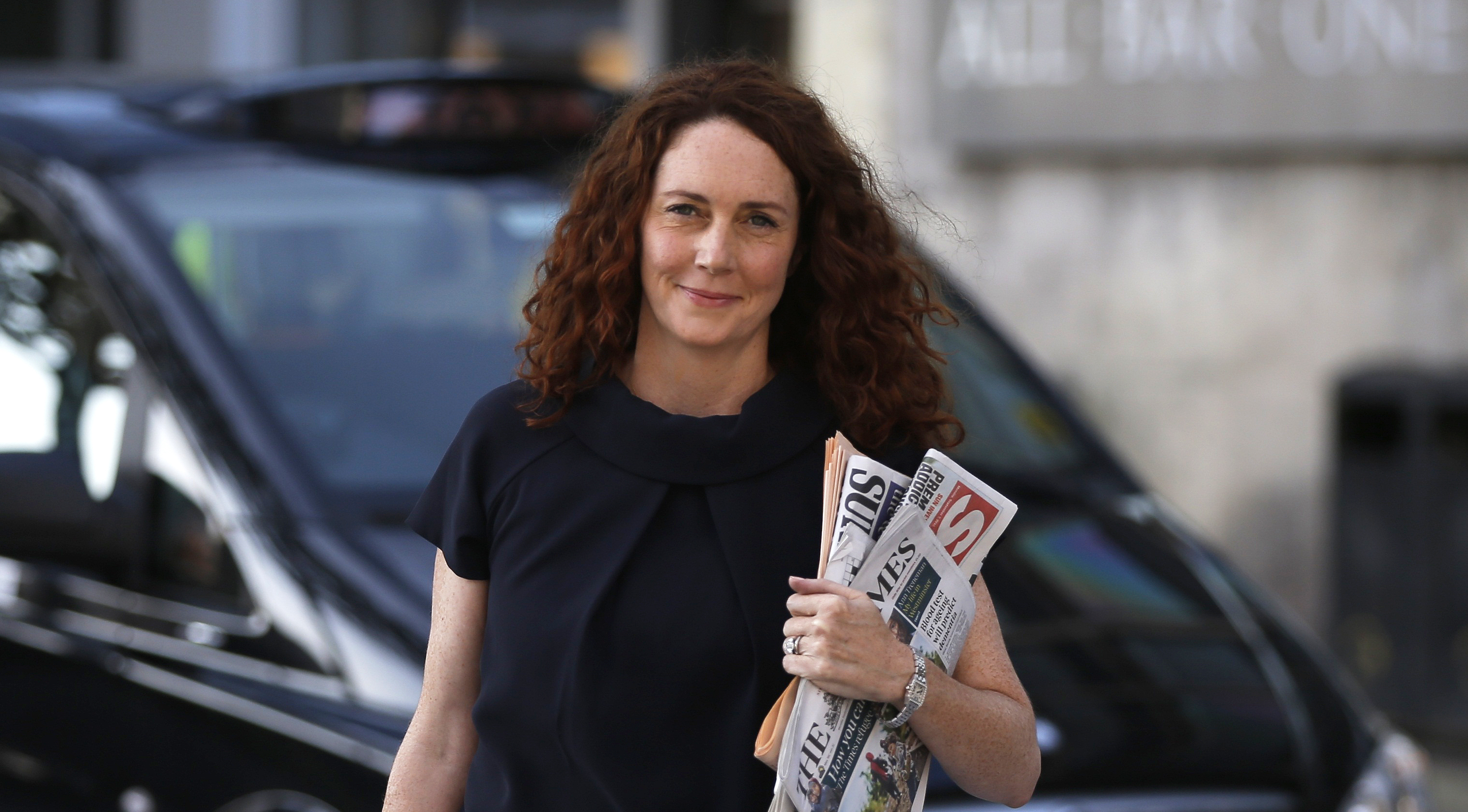 A wide shot of a woman walking on a city street carrying several periodicals