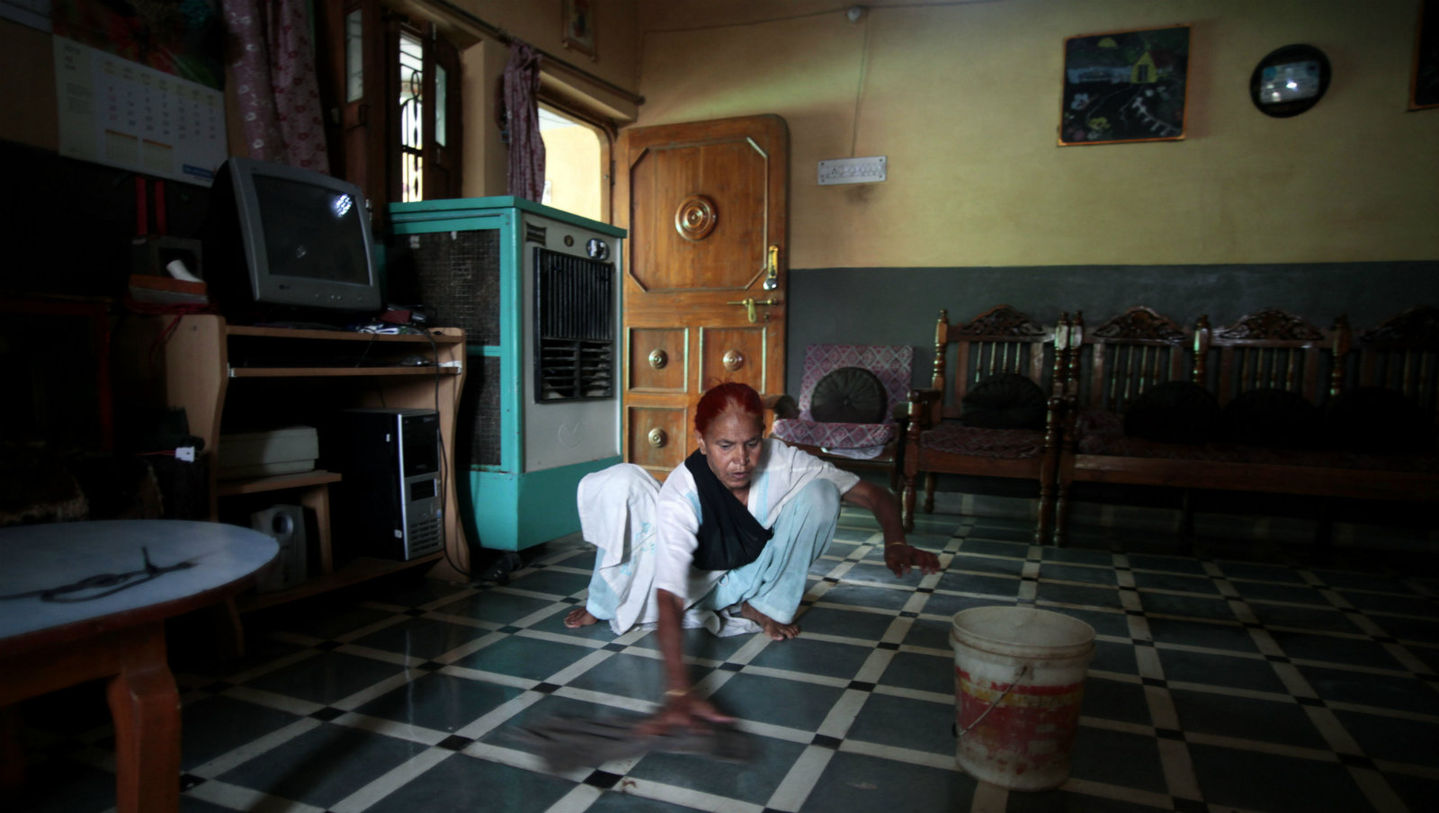 In this May 10, 2012 photo, Fatima Munshi, working as domestic help, cleans a floor in a home in Khandwa, India. Saroo Brierley, 30, was reunited with his biological mother, Munshi, in February 2012, 25 years after an ill-fated train ride left him an orphan on the streets of Calcutta.