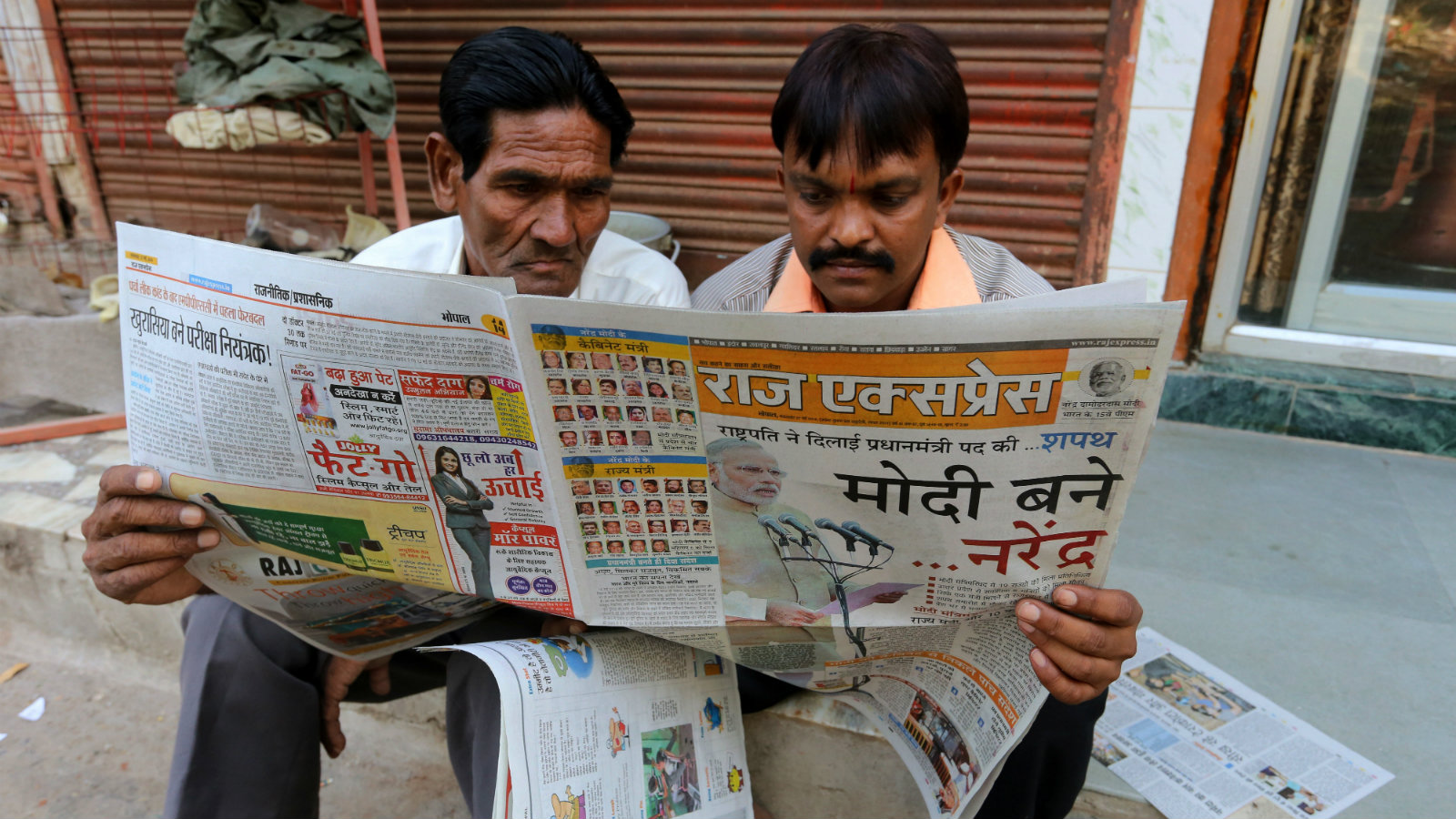 Indian men reads a Hindi newspaper with the headlines of Narendra Modi swearing-in as Prime Minister of India, in Bhopal, India on 27 May,2014.Narendra Modi was sworn in as India's 15th prime minister on 26 May 2014 in a ceremony attended by leaders of neighbouring countries including Pakistan and Afghanistan.