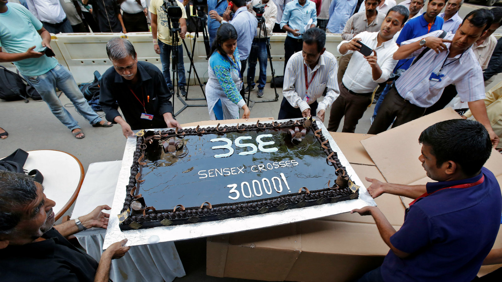 Employees of the Bombay Stock Exchange (BSE) carry a cake outside the building for the celebrations marking the Sensex index rising over 30,000, in Mumbai, India April 26, 2017.