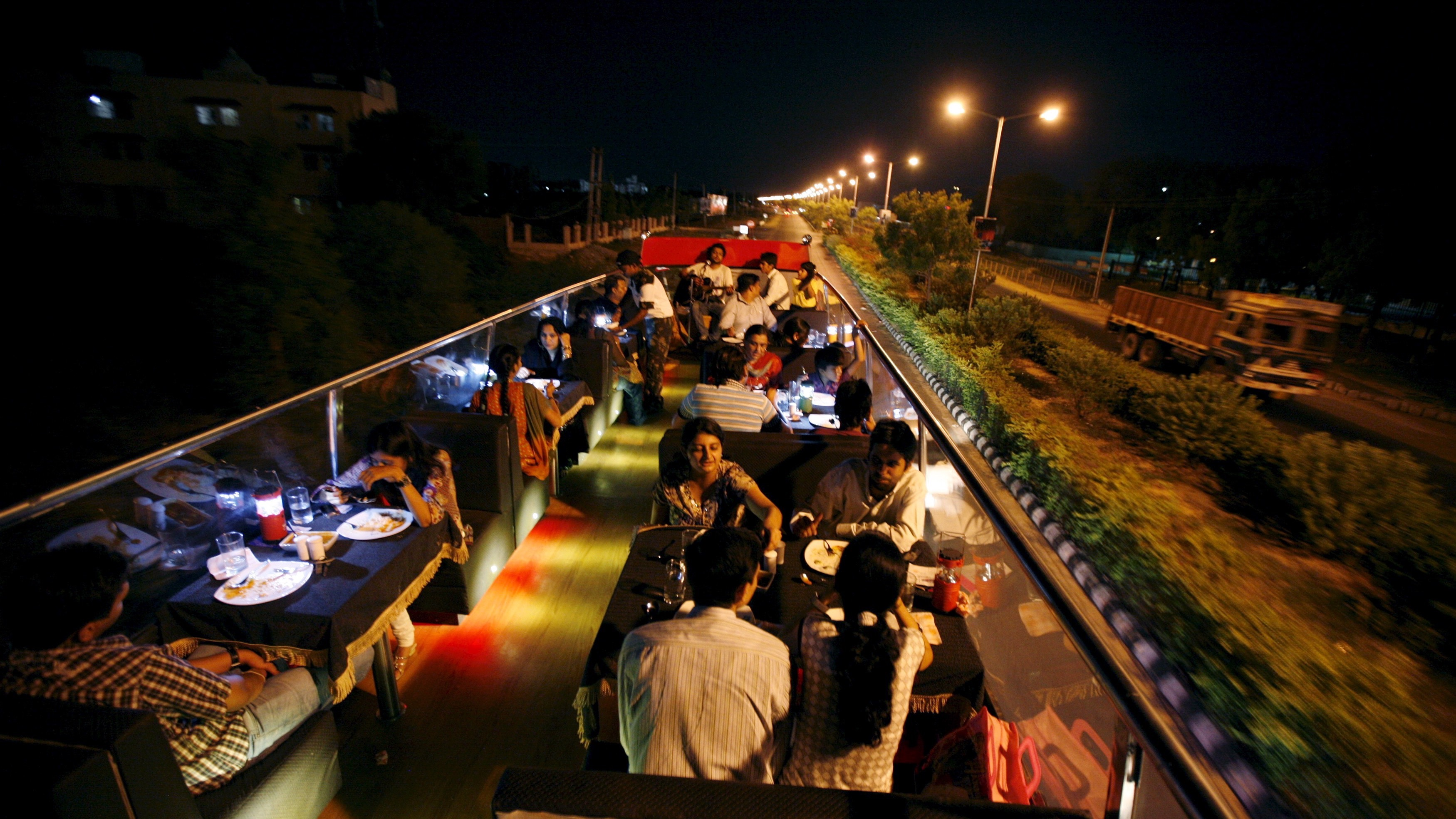 People dine on a double-decker bus which has been converted to a mobile restaurant as it travels through the streets of Ahmedabad