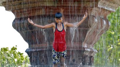 A boy plays in a fountain on a hot summer's day in New Delhi