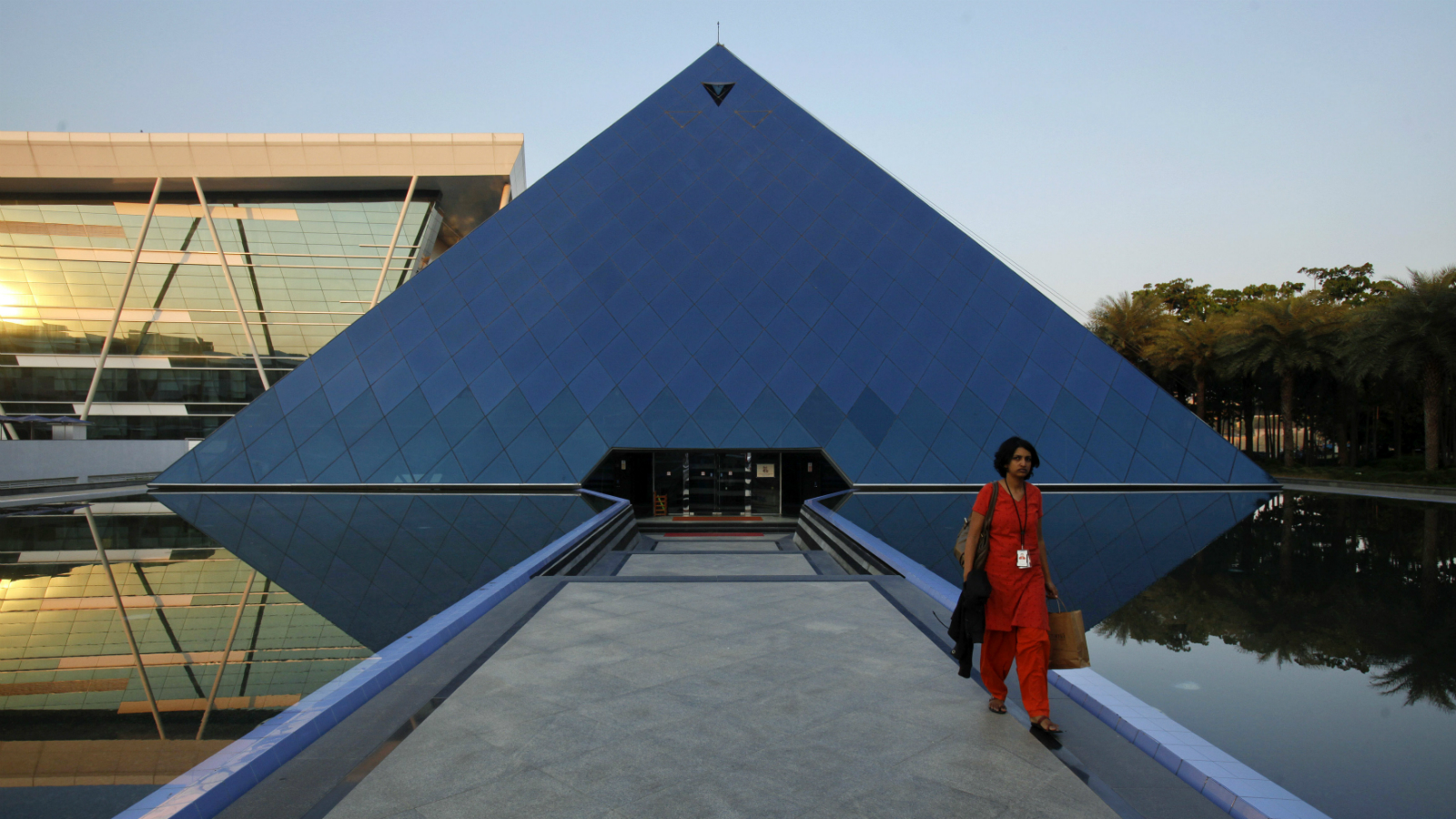 An employee walks out of an iconic pyramid-shaped building made out of glass in the Infosys campus at Electronics City in Bangalore, February 28, 2012. Picture taken on February 28, 2012.