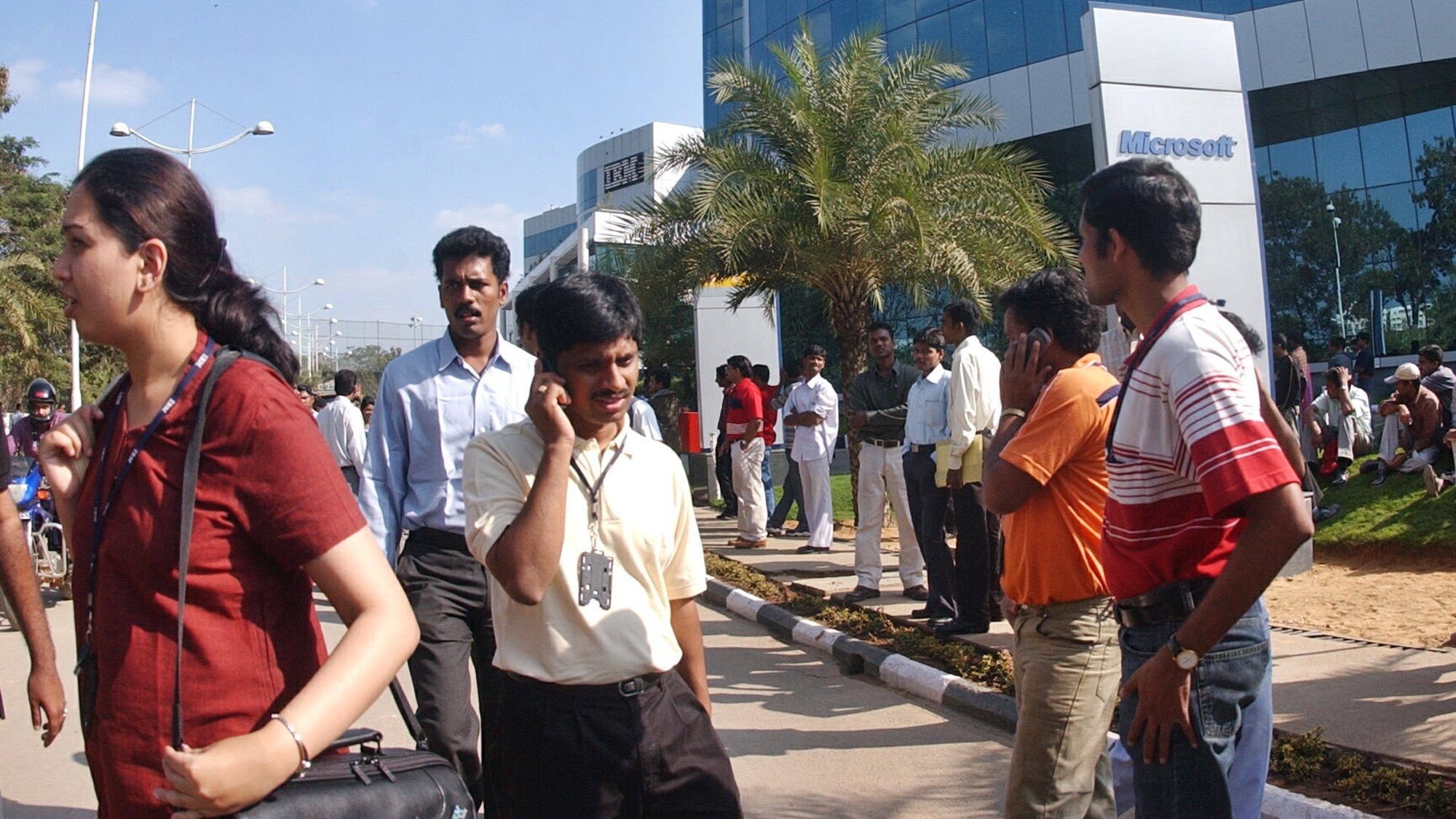 Anxious workers leave a building that has offices of international companies like Microsoft and IBM, after an anonymous caller informed about the presence of a bomb which later turned out to be a false, at Bangalore, India, Friday Dec. 30, 2005. High-tech firms, the Indian space agency and nuclear facilities stepped up security Friday after an unknown group threatened suicide attacks against a top politician and New Year's revelers in India's technology hub, officials said.  (AP Photo)