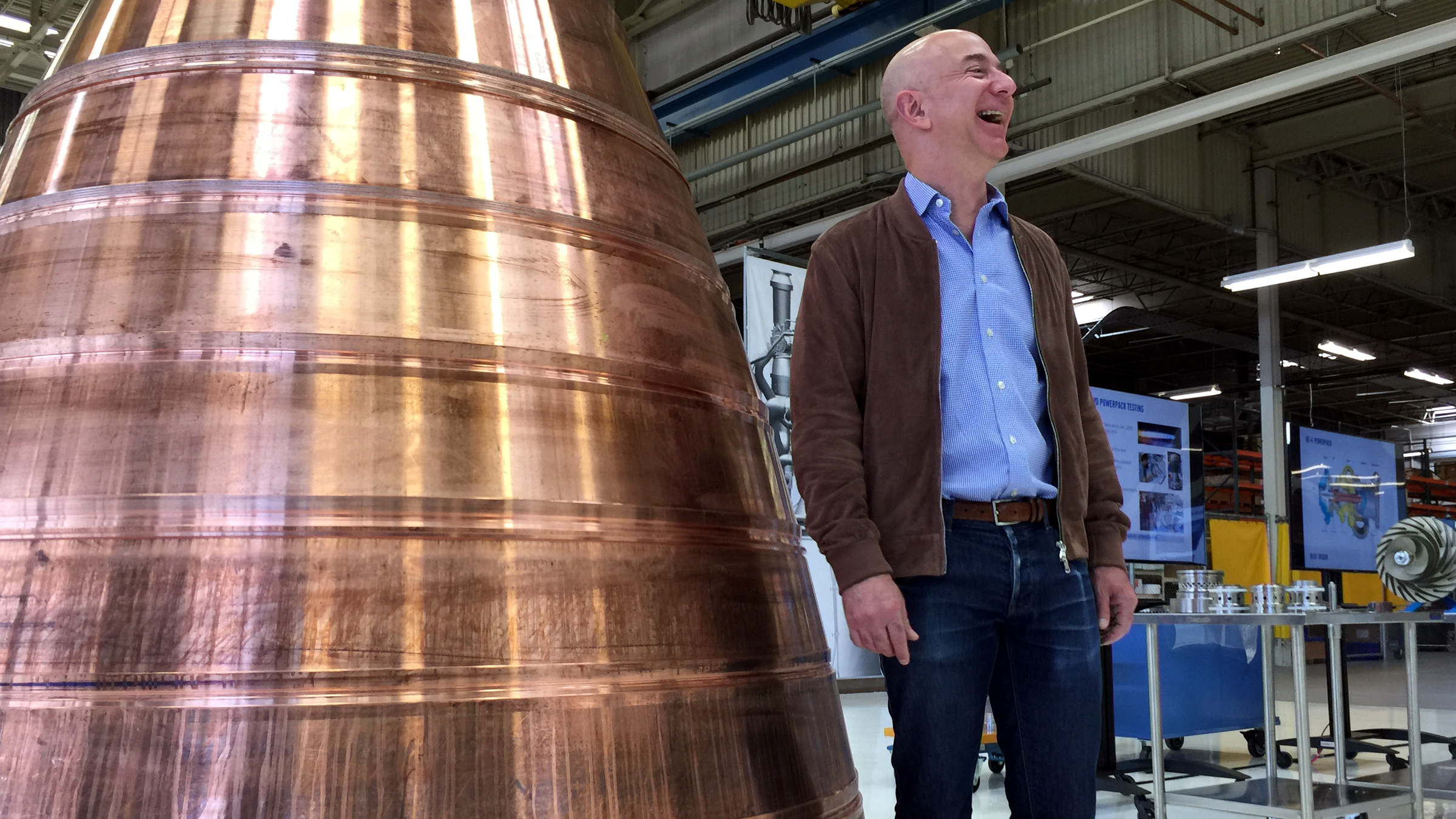 Amazon.com founder Jeff Bezos stands next to a copper exhaust nozzle to be used on a space ship engine during a media tour of Blue Origin, the space venture he founded, Tuesday, March 8, 2016, in Kent, Wash. The private space company opened its doors to the media for the first time on Tuesday to give a glimpse of how organizations like Blue Origin are creating the next generation of rockets for private and public use.