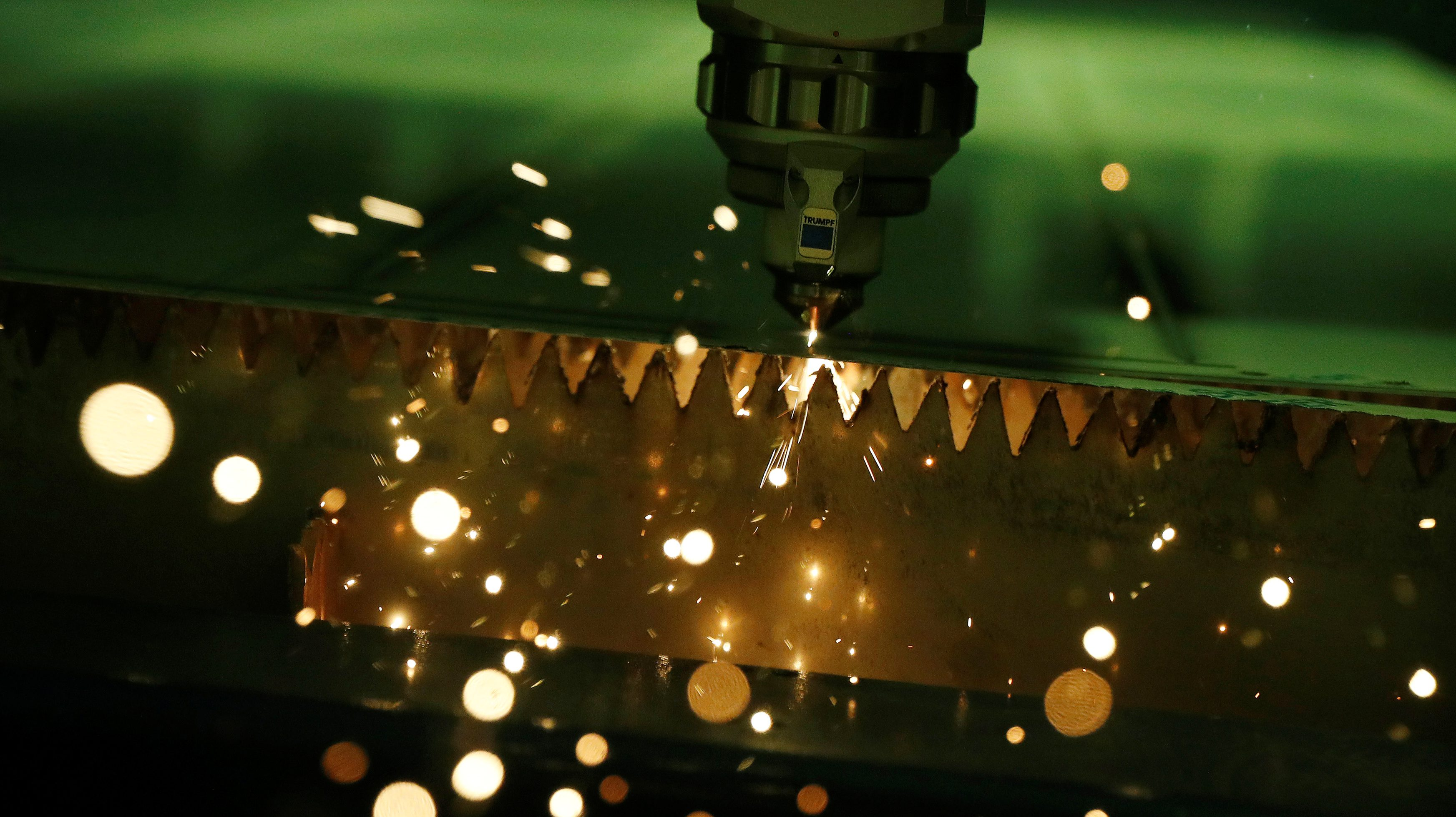 A laser cutter produces sparks as it cuts a sheet of steel into components at the Mec Com Ltd factory near Stafford, central England December 15, 2016. Picture taken December 15, 2016.