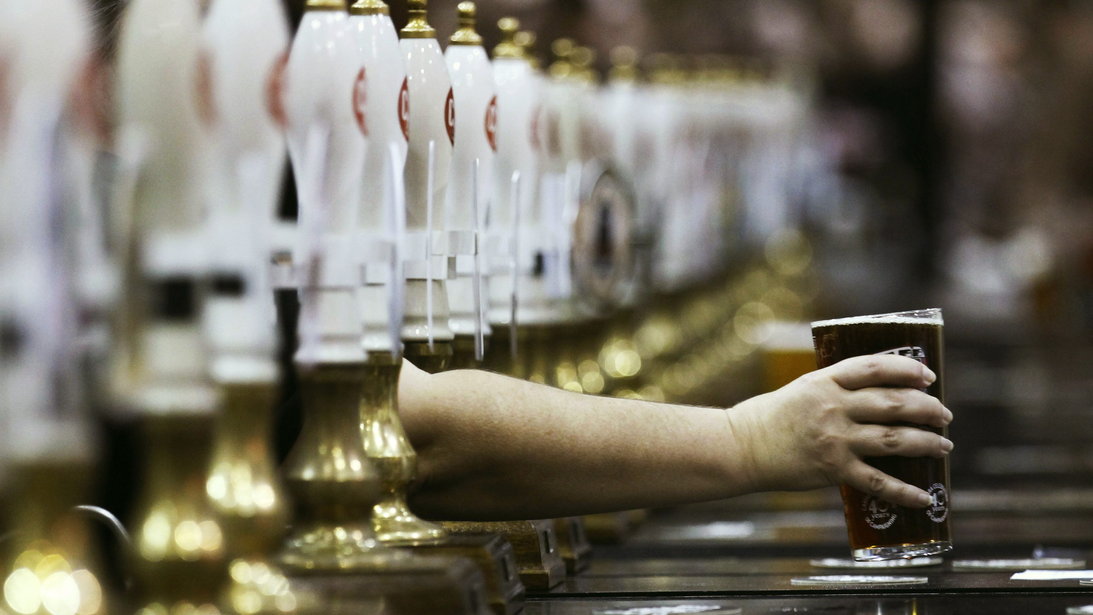 A pint of beer is served through rows of beer pumps at the Campaign For Real Ale Great British Beer Festival at Earls Court in London August 2, 2011. British pubs -- closing at record rates in a harsh economic climate -- could be saved by reviving traditional games like skittles and darts, according to a report on Tuesday. Such games have disappeared from many pubs in recent years in favour of gaming machines which charge customers to play, and from which landords can take a cut, the report said.  To match Reuters Life! BRITAIN-PUBS/