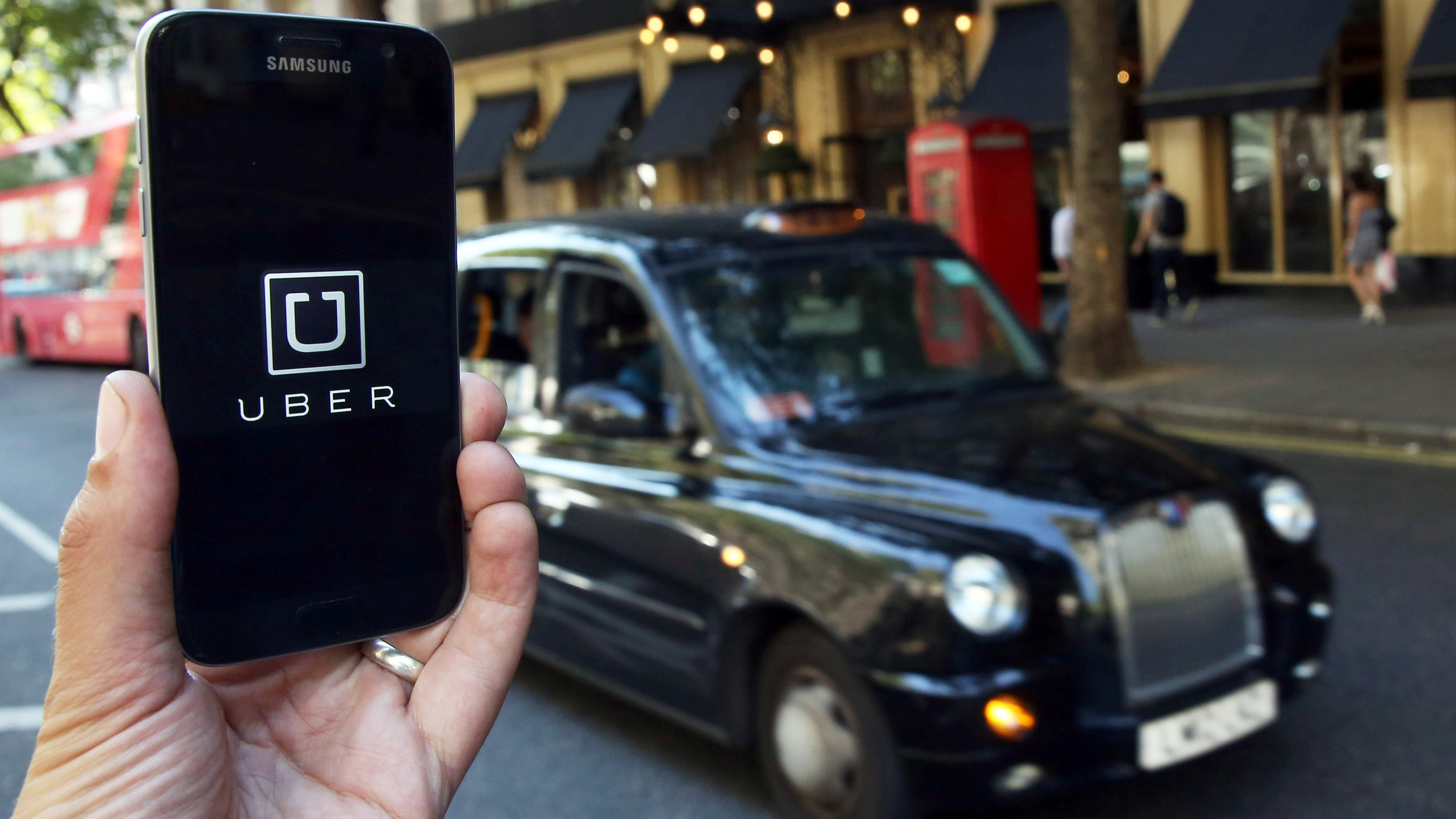 FILE PHOTO - A photo illustration shows the Uber app logo displayed on a mobile telephone, as it is held up for a posed photograph in central London, Britain August 17, 2016.