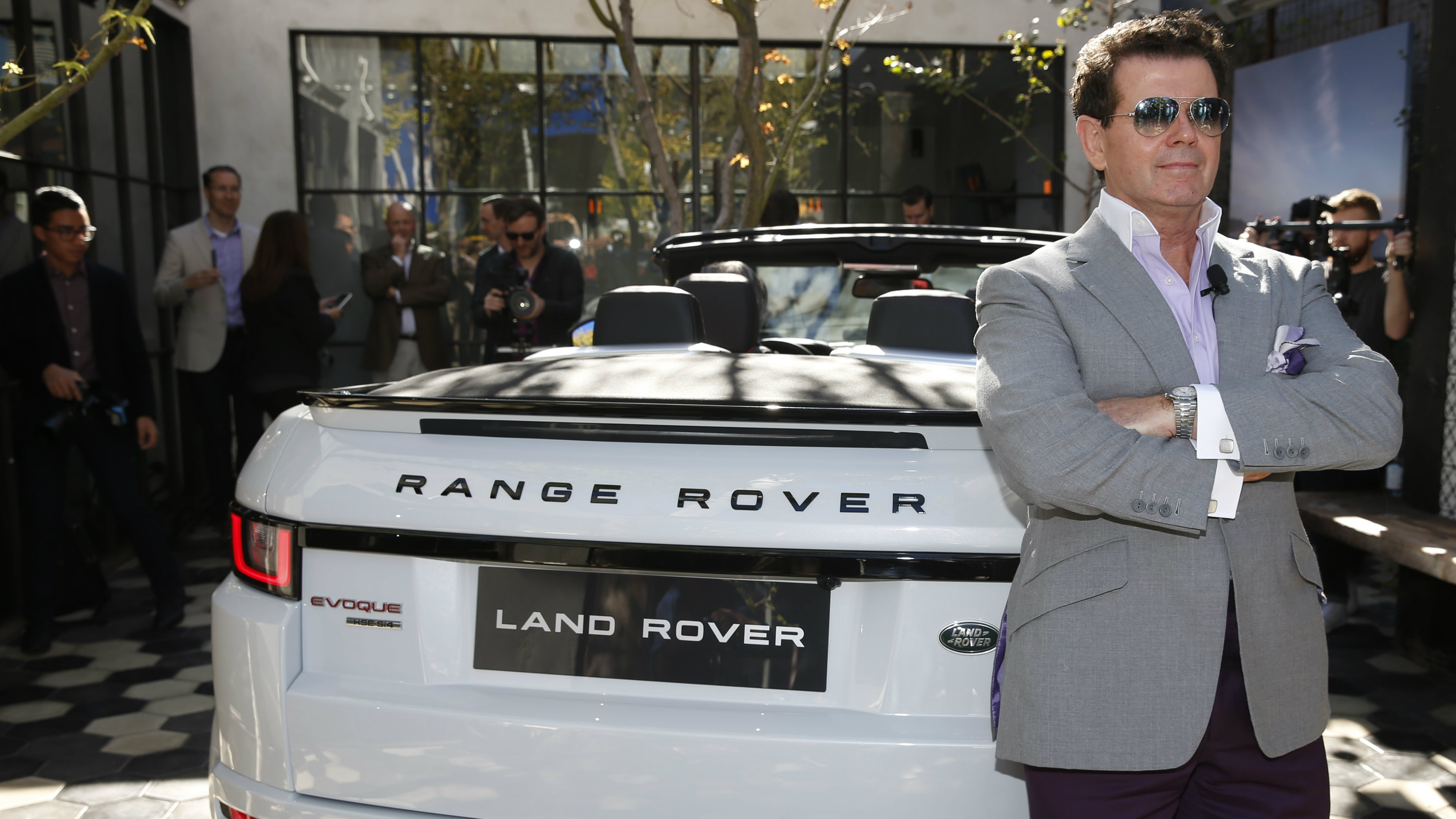 A man poses in front a Range Rover.