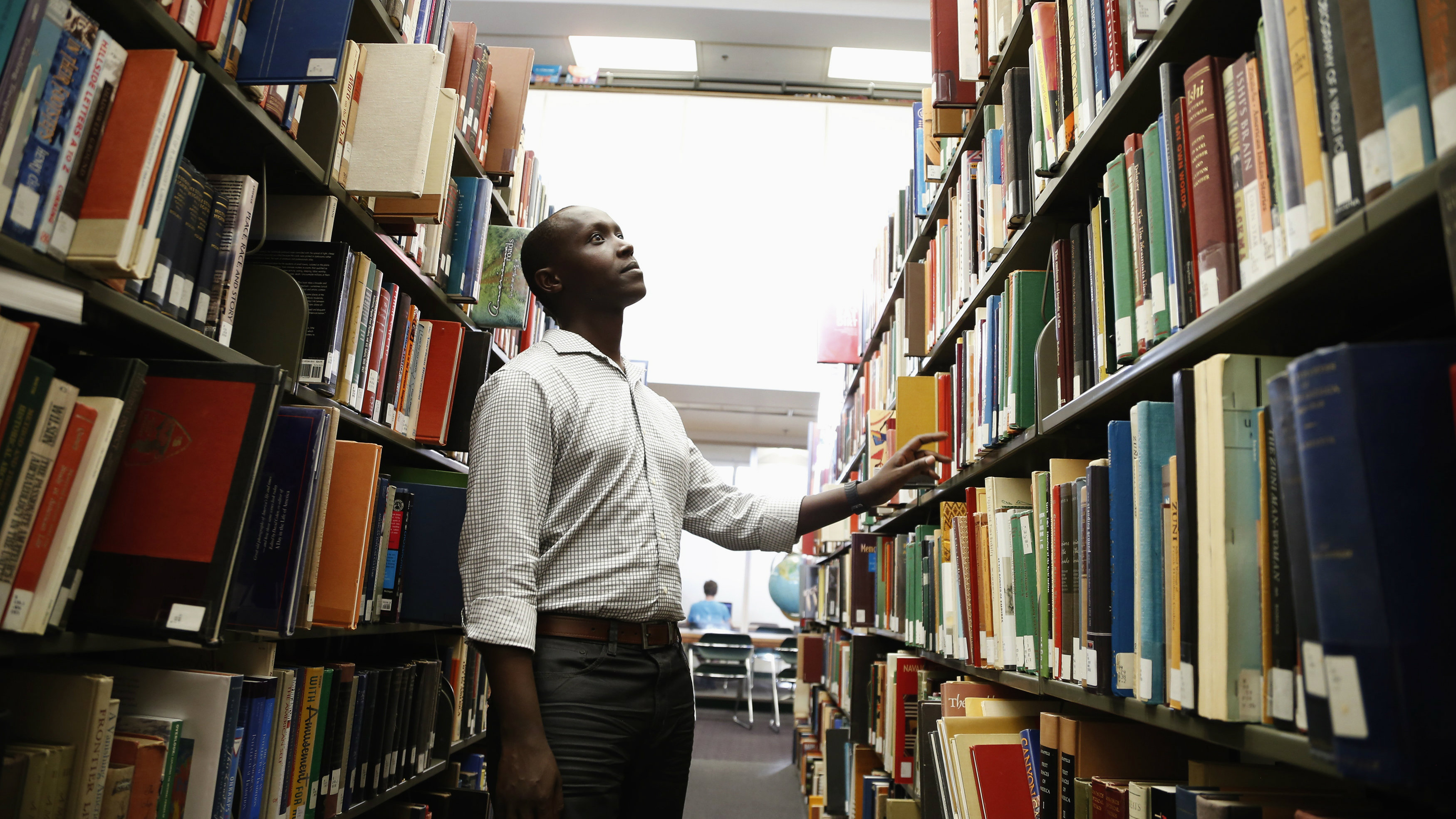 Patrick Manyika, 33, of Rwanda looks for a book in the library at the University of Redlands where he will starting his second master's degree in Geographic Information Systems, in Redlands, California May 28, 2014. Manyika was born in a Ugandan refugee camp after his Tutsi family fled Rwanda. In 1983, unrest forced them back to Rwanda, where they lived first in a national park, then in the capital. Manyika survived the Rwandan genocide of 1994, in which 800,000 Tutsis and moderate Hutus were killed, by sheltering in a UN-controlled soccer stadium. After doing charity work and teaching himself various languages, in 2009 he had the opportunity to leave Rwanda and pursue his education in the United States. He is now about to start his second Masters degree. June 20 is World Refugee Day, an occasion that draws attention to those who have been displaced around the globe. In the run-up to the date, Reuters photographers in different regions have photographed various people who have at some point fled their homes. Picture taken May 28, 2014. REUTERS/Lucy Nicholson (UNITED STATES - Tags: SOCIETY IMMIGRATION POLITICS EDUCATION)