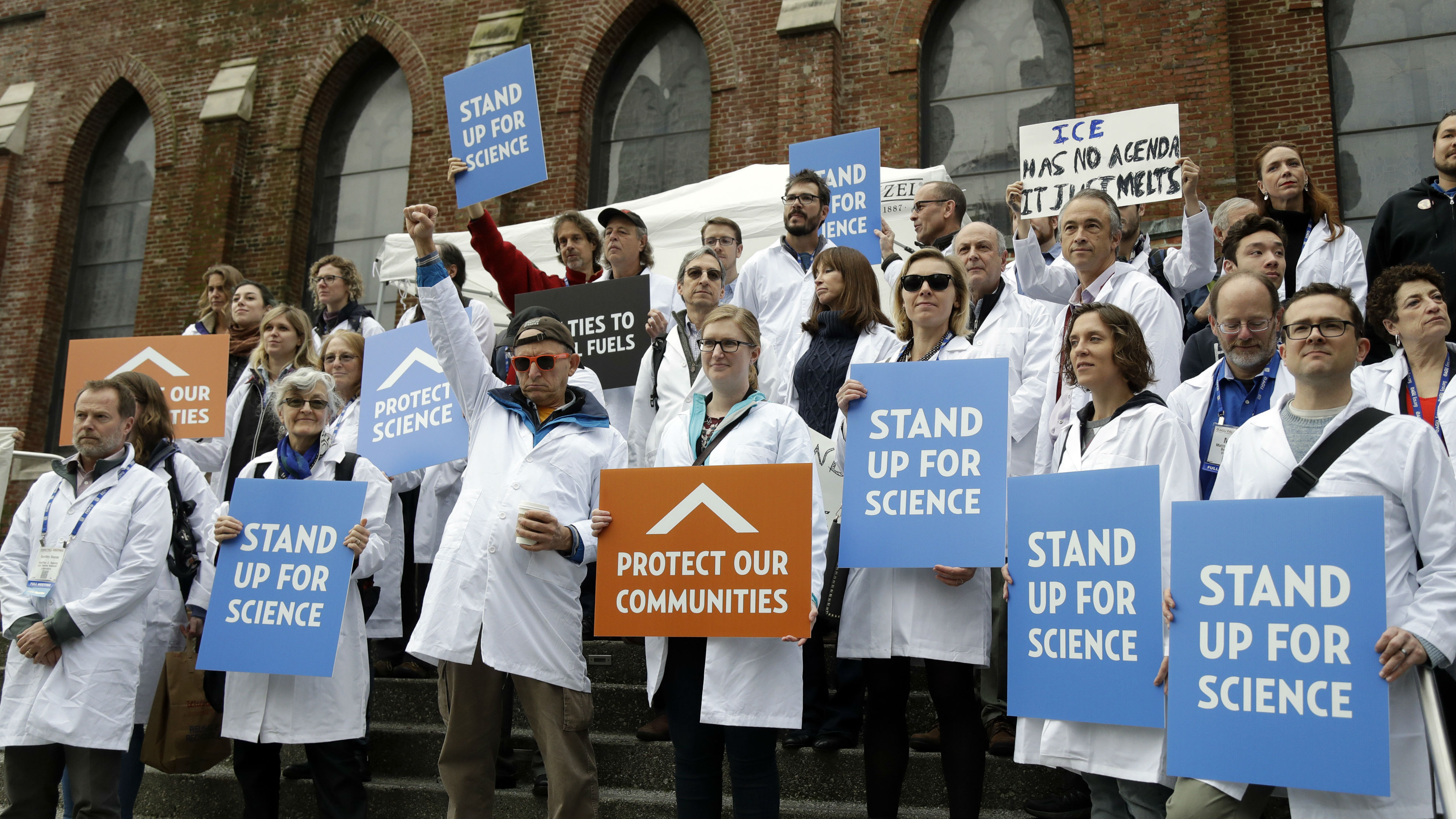 Scientists hold signs during a rally in conjunction with the American Geophysical Union's fall meeting Tuesday, Dec. 13, 2016, in San Francisco. The rally was to call attention to what scientist believe is unwarranted attacks by the incoming Trump administration against scientists advocating for the issue of climate change and its impact.