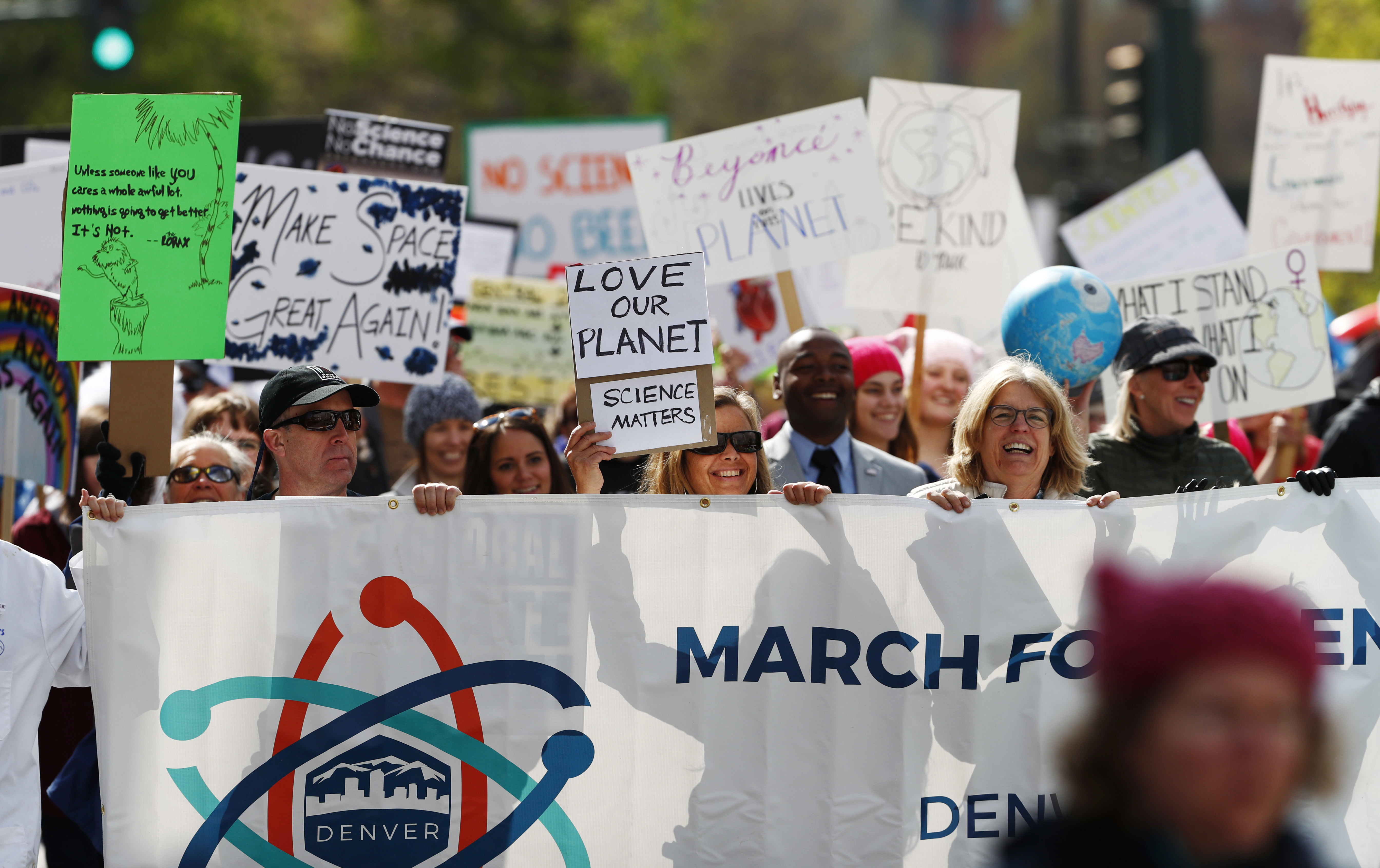 A large crowd marching for science with a banner in front of them and many signs.