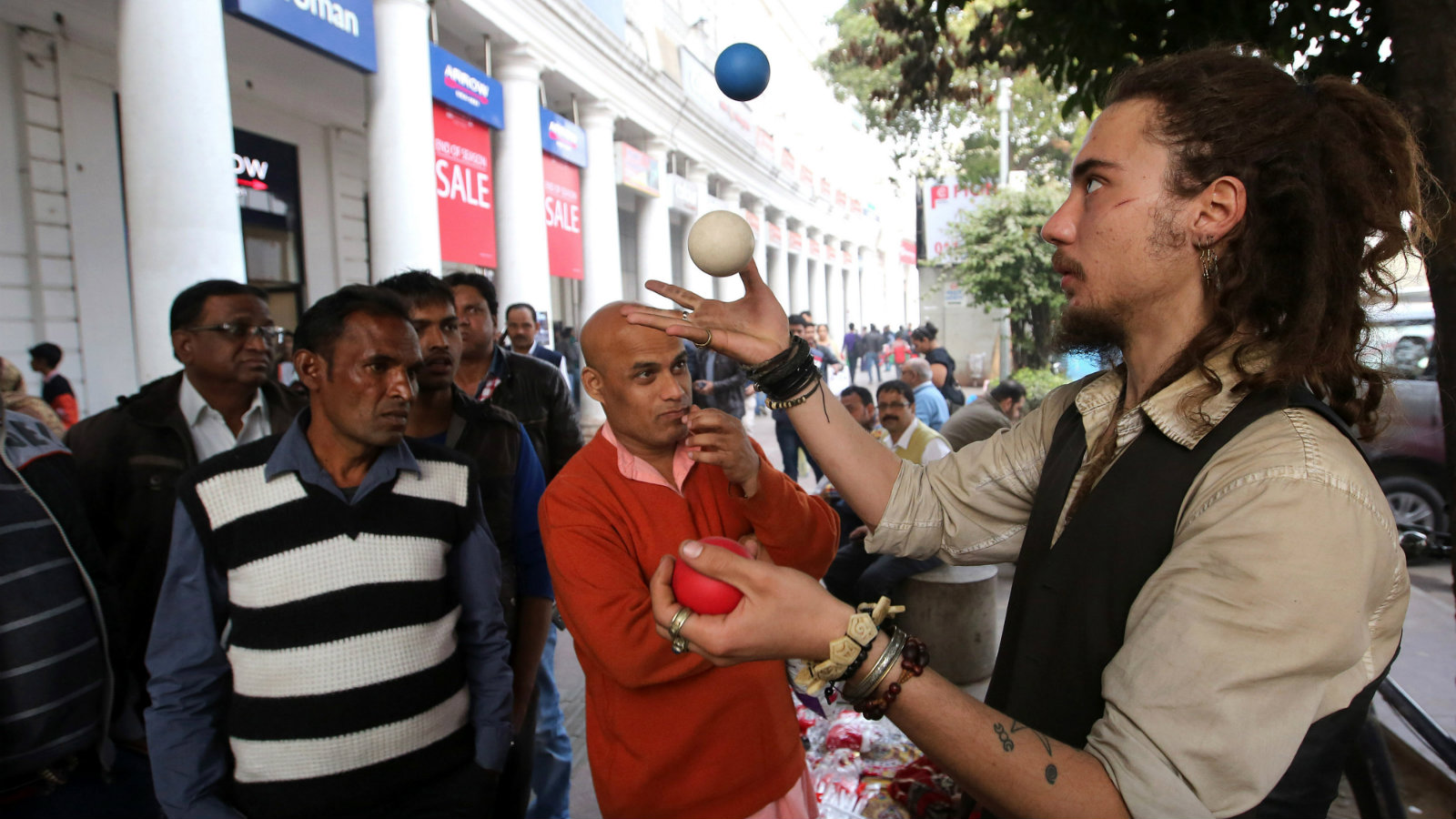 A man, who identifies himself as Spanish citizen named Remo, juggles balls purportedly to collect money to fly back to his home country, at Connaught place in New Delhi, India, 24 December 2016. According to the man, he arrived in India on 28 November from Barcelona, Spain, where his money was stolen from New Delhi Railways Station. For the last few days he has been juggling balls to collect money for his return ticket.