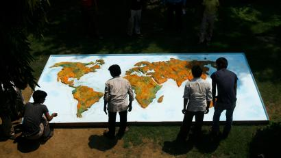 men in india look at map of the world