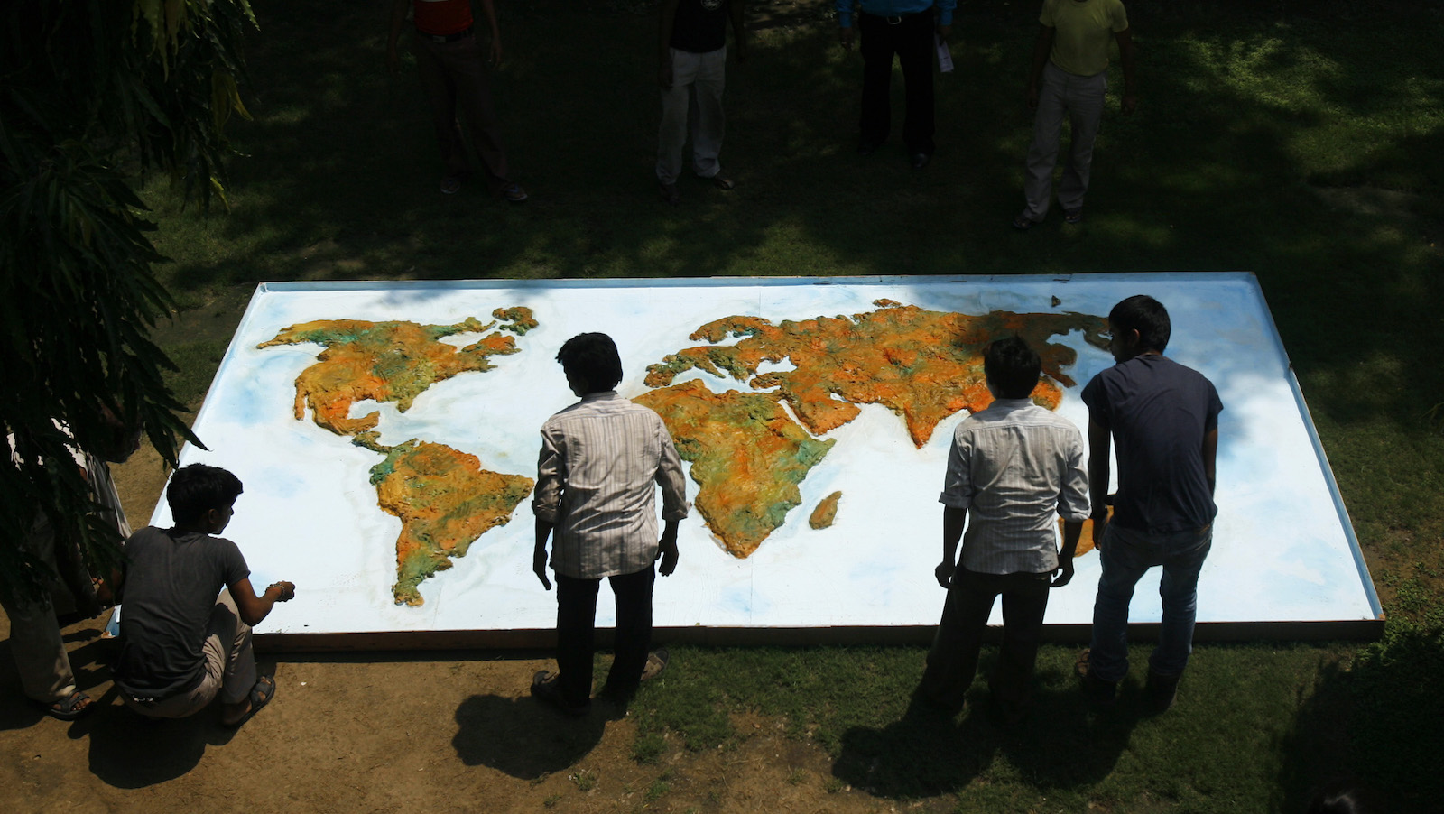 Workers place a hoarding with the world map before the start of a press conference in New Delhi, India, Friday, Aug. 28, 2009. The press conference was organized by various non government organizations to mark the hundred days countdown to the Copenhagen summit. (AP Photo/Manish Swarup)