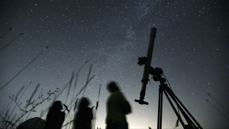 three people watch meteor shower