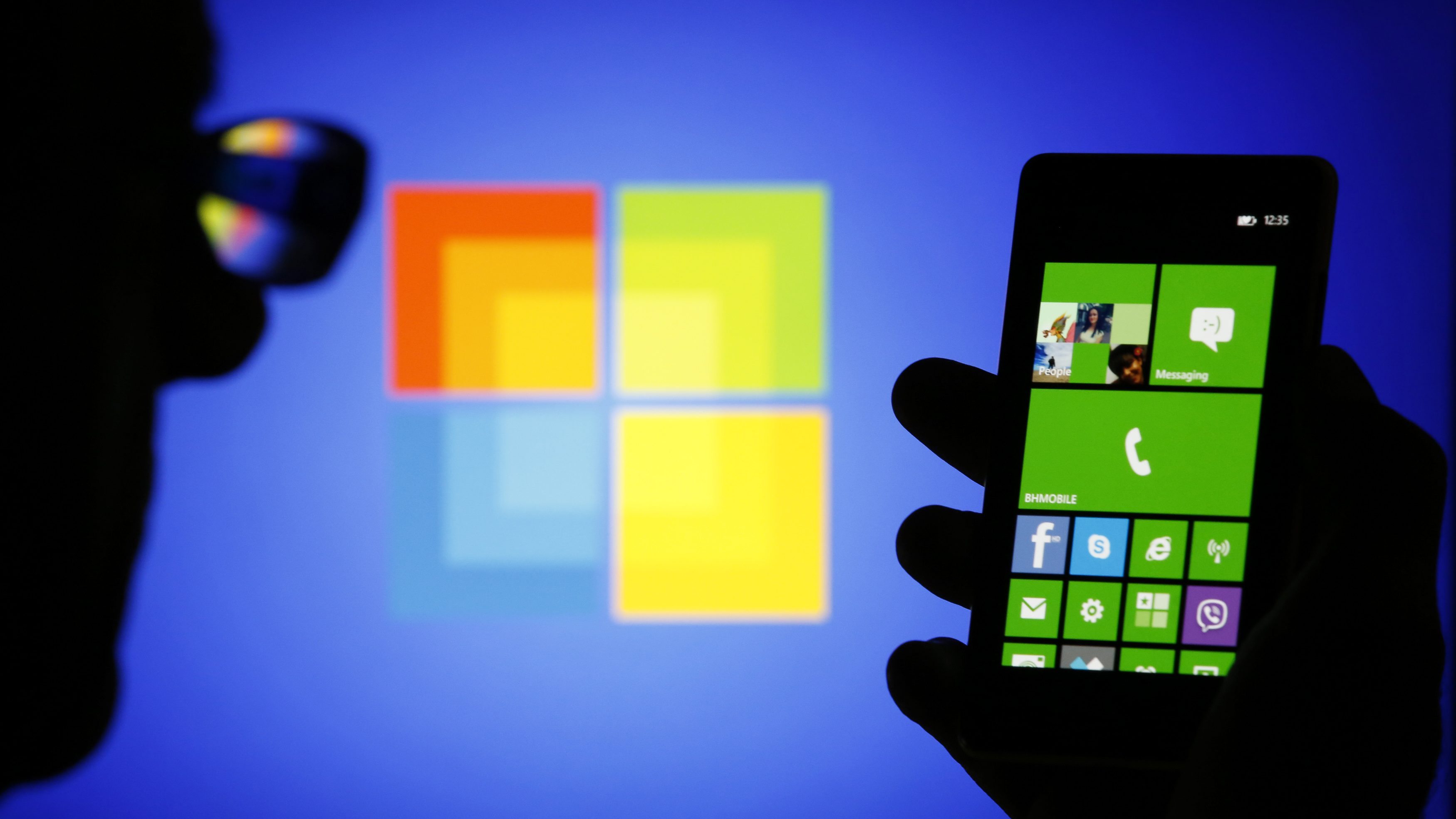 A man is silhouetted against a video screen with as he poses with a Nokia Lumia 820 smartphone in this photo illustration taken in the central Bosnian town of Zenica, September 3, 2013. Two years after hitching its fate to Microsoft's Windows Phone software, a withered Nokia collapsed into the arms of the U.S. software giant, agreeing to sell its main handset business for 5.44 billion euros ($7.2 billion). Nokia, which will continue as a maker of networking equipment and holder of patents, was once the world's dominant handset manufacturer but was long since overtaken by Apple and Samsung in the highly competitive market for more powerful smartphones.