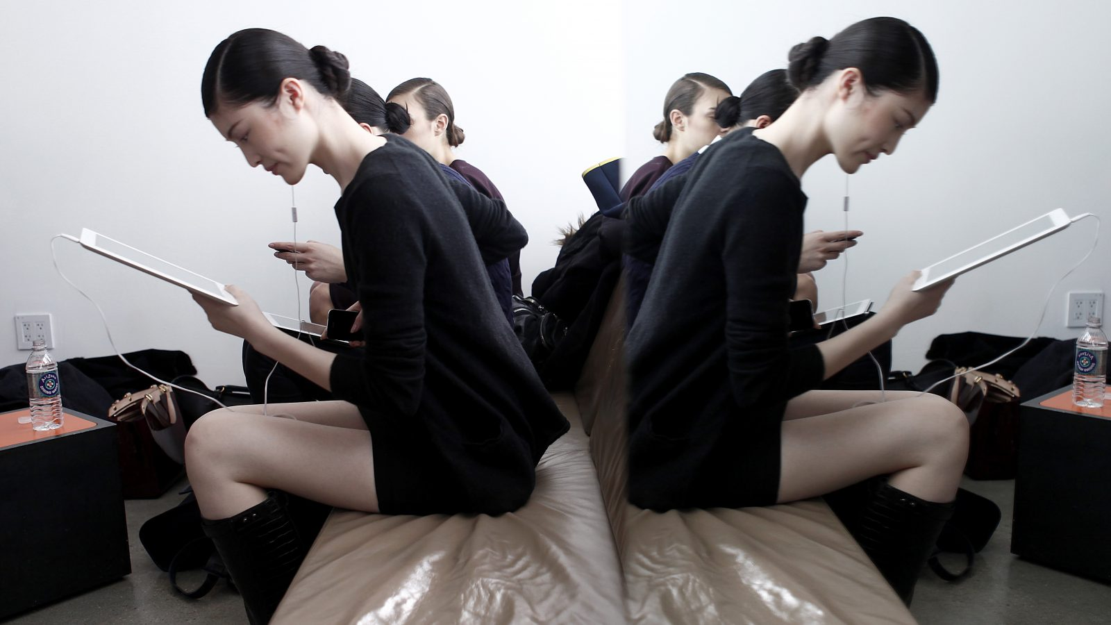 A model is seen reflected in a mirror while she reads her iPad backstage before the Peter Som Fall/Winter 2012 collection show during New York Fashion Week, February 10, 2012.