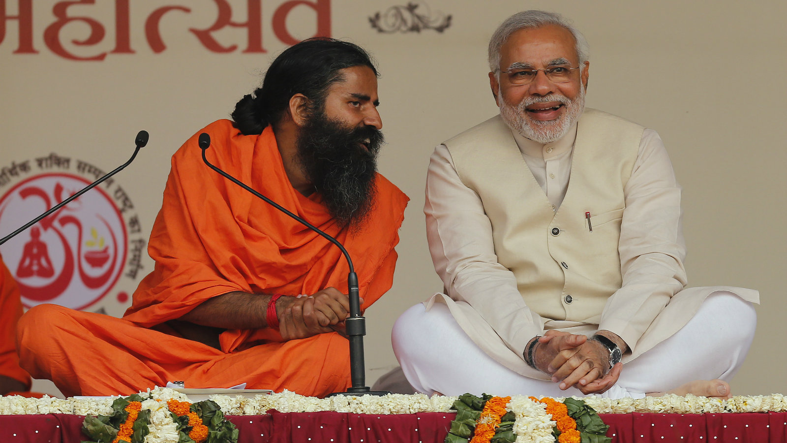 Hindu nationalist Narendra Modi, prime ministerial candidate for India's main opposition Bharatiya Janata Party (BJP) shares a moment with Indian yoga guru Baba Ramdev (L) during a Yoga Mahotsav or festival, in New Delhi March 23, 2014. The mega 'Yoga Mahotsav' on Sunday is being observed simultaneously at various places across the country, local media reported. i